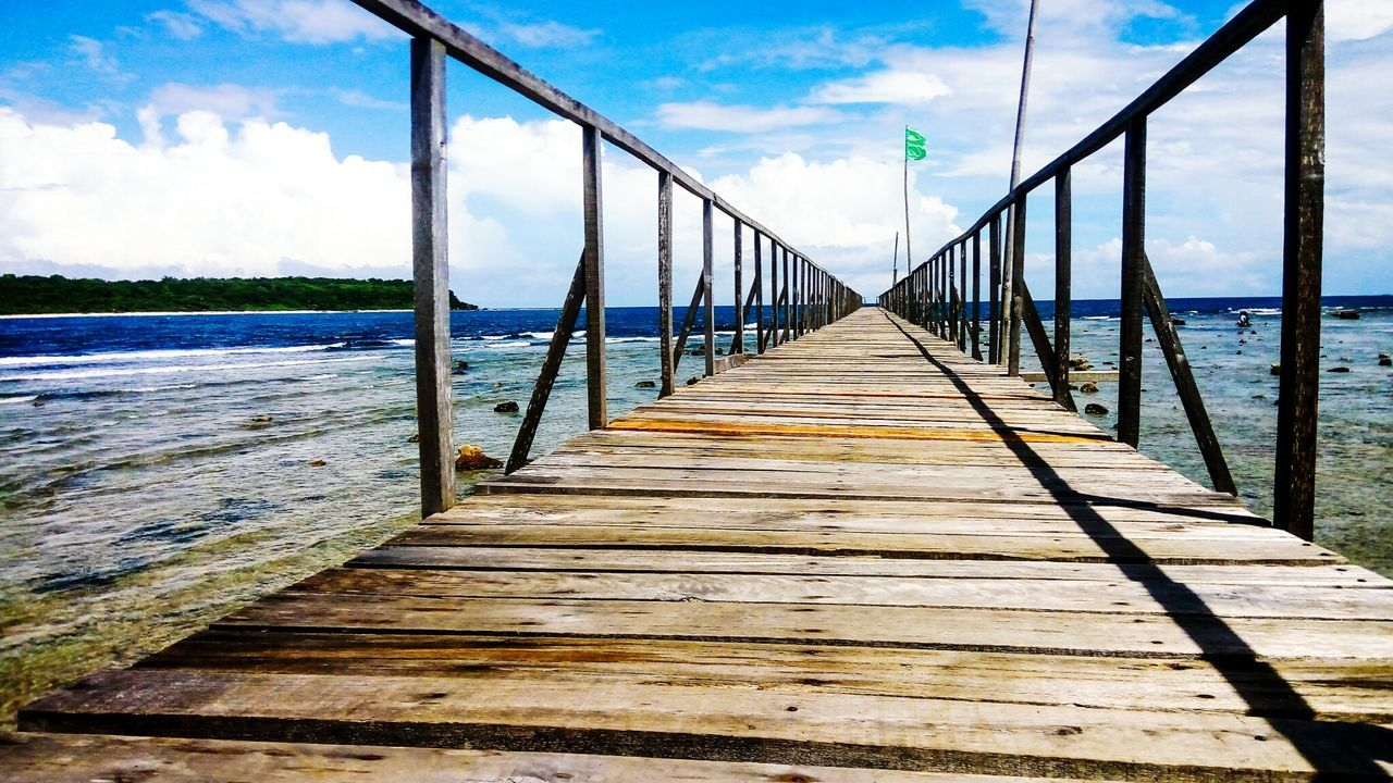cloud - sky, sky, water, wood - material, railing, wood paneling, bridge - man made structure, nature, the way forward, day, outdoors, tranquil scene, built structure, no people, beauty in nature, tranquility, scenics, sea, footbridge, architecture, tree