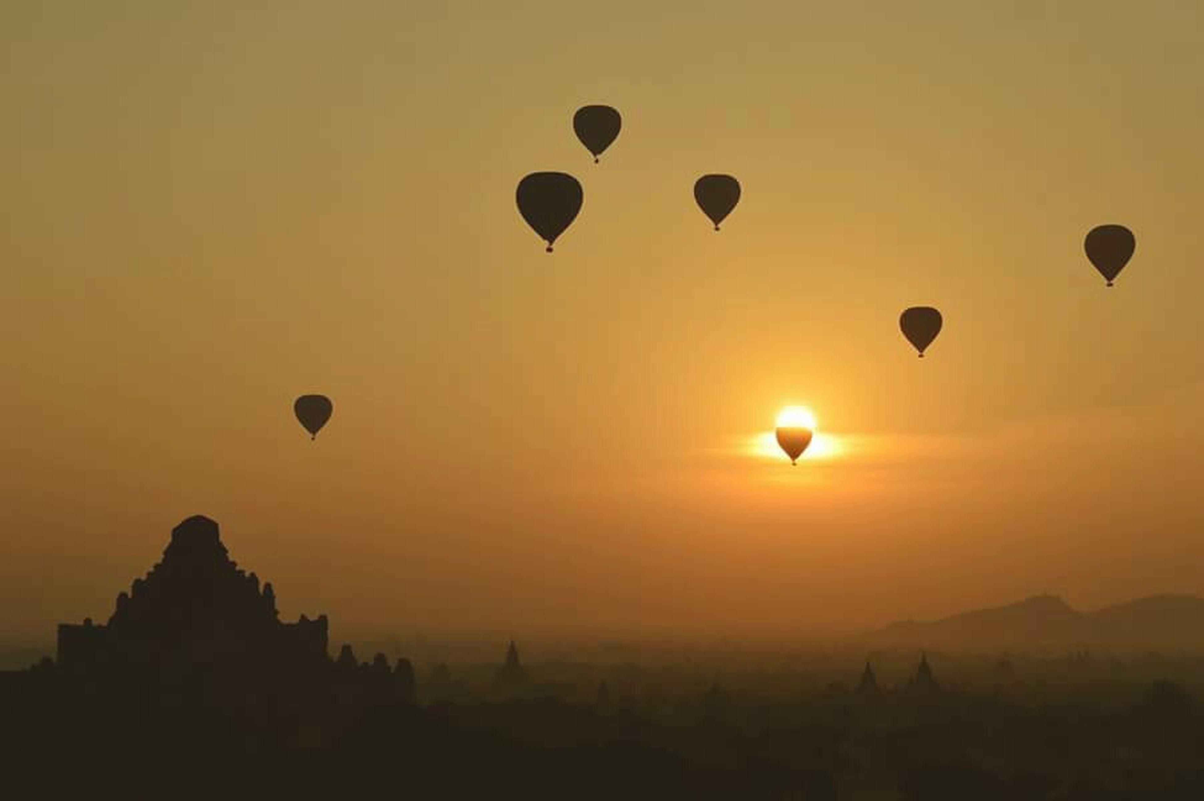 sunset, hot air balloon, flying, scenics, sun, orange color, mid-air, sky, tranquil scene, beauty in nature, tranquility, silhouette, landscape, nature, idyllic, parachute, outdoors, copy space, travel, transportation
