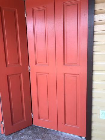 A Bi-fold painted door partly open. The Purist (no Edit, No Filter) Outdoor Photography Focus On Foreground Getting Creative Check This Out Capture The Moment Popular Photos The Week on EyeEm EyeEmBestPics EyeEm Best Shots EyeEmNewHere Hinge Salmon Colored Door Painted Bi-fold Door EyeEm Selects Door Safety No People Architecture Wood - Material Protection Built Structure Day Outdoors Close-up