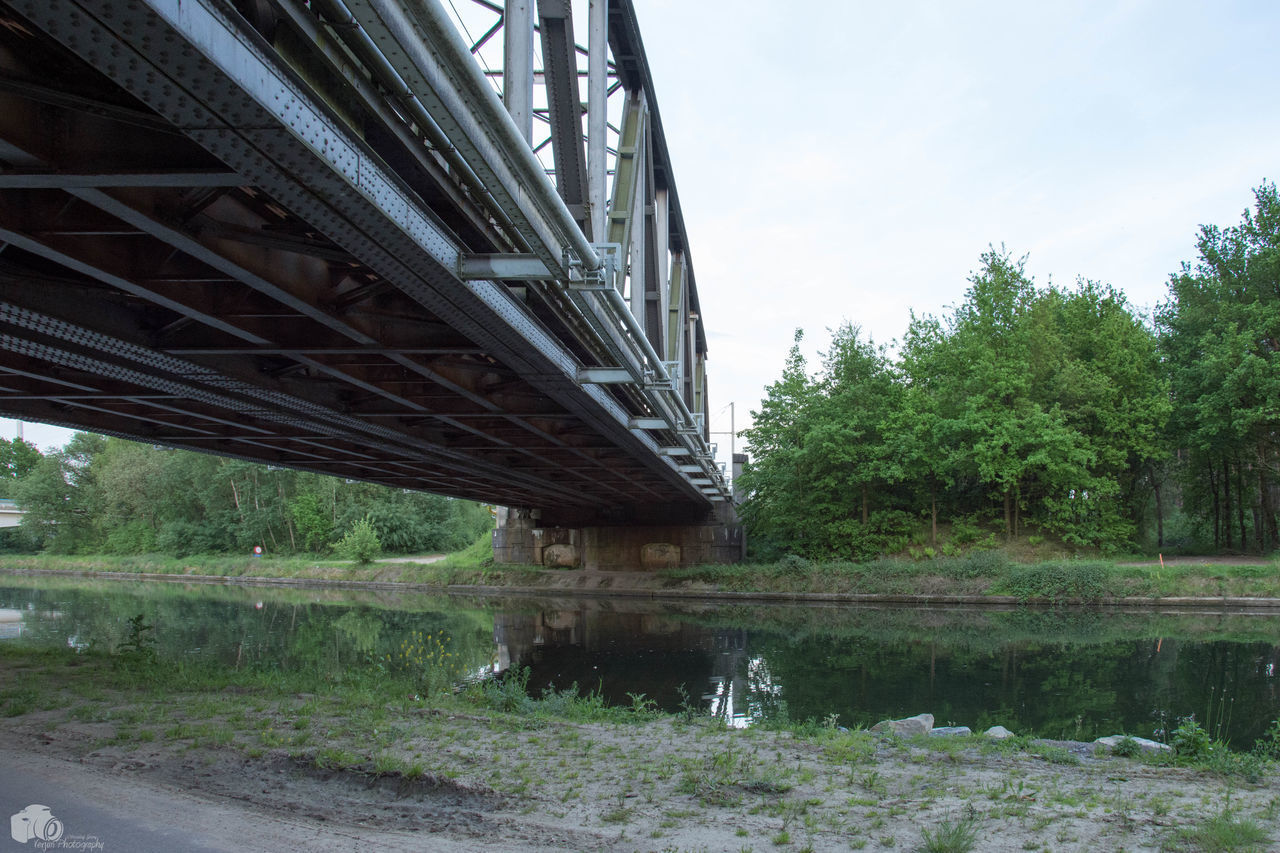 bridge - man made structure, connection, architecture, engineering, built structure, transportation, water, underneath, below, river, bridge, railroad bridge, outdoors, day, no people, sky, tree