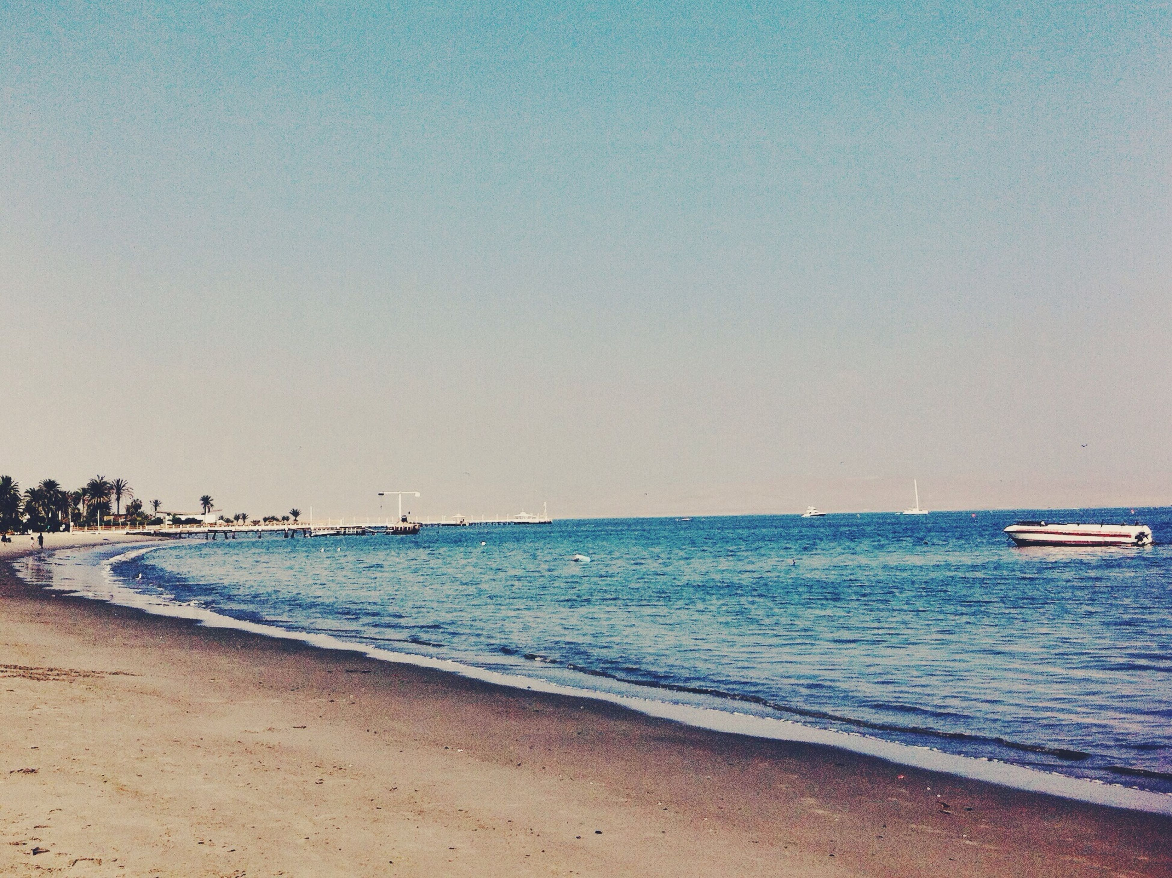 sea, beach, water, clear sky, copy space, shore, sand, horizon over water, tranquility, tranquil scene, nautical vessel, scenics, nature, beauty in nature, incidental people, coastline, transportation, boat, outdoors, idyllic