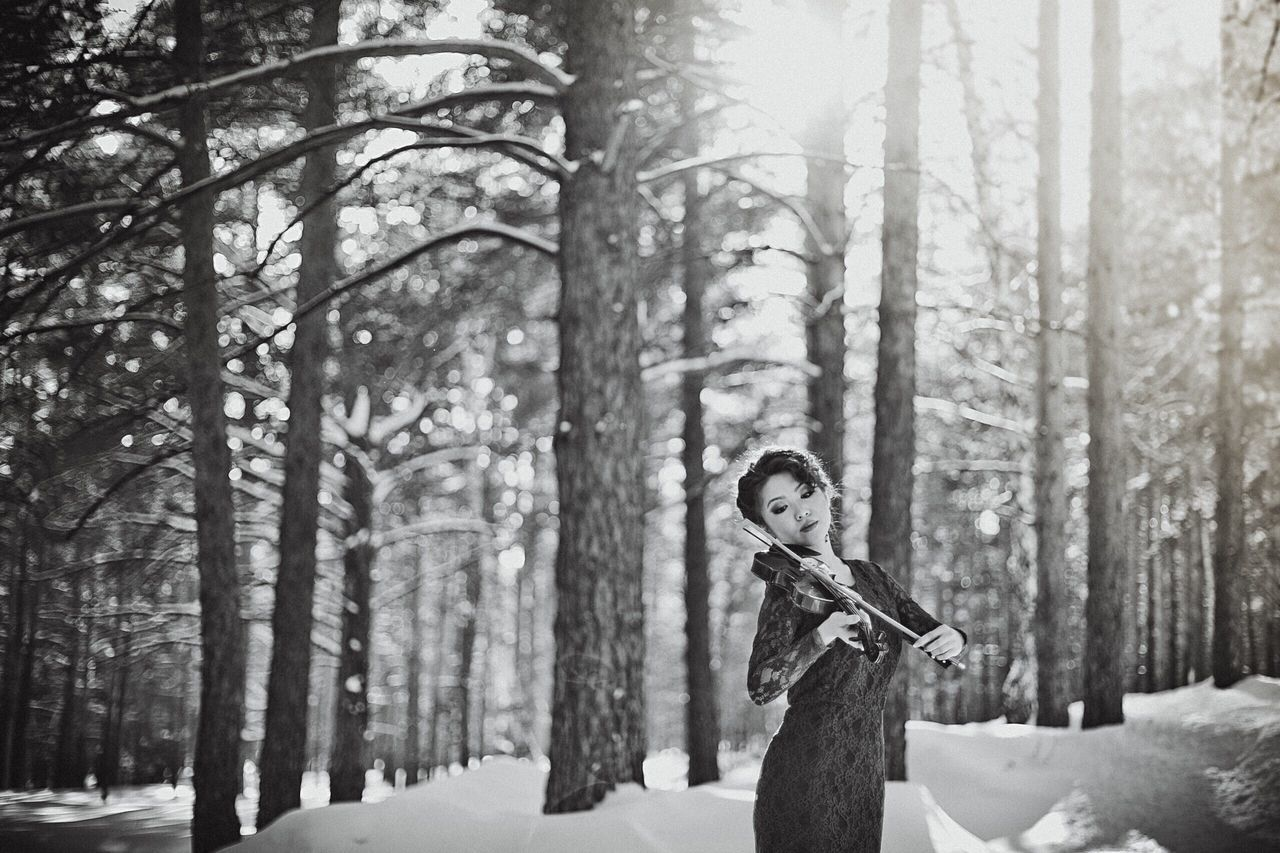 snow, winter, forest, cold temperature, tree, nature, tree trunk, one person, woodland, outdoors, musical instrument, day, young adult, women, beauty in nature, warm clothing, young women, adult, full length, adults only, one woman only, musician, people