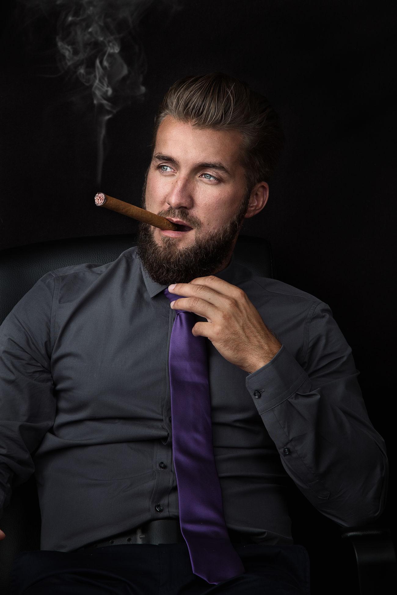 Portrait of a young successful businessman smoking a cigar on black background Attractive Beard Black Background Boss Business Cigar Cigarette  Cloud Holding Indoors  Isolated Lifestyles Luxury Mafia  Man Model One People Person Portrait Rich Smoking Stylish Successful Young Adult