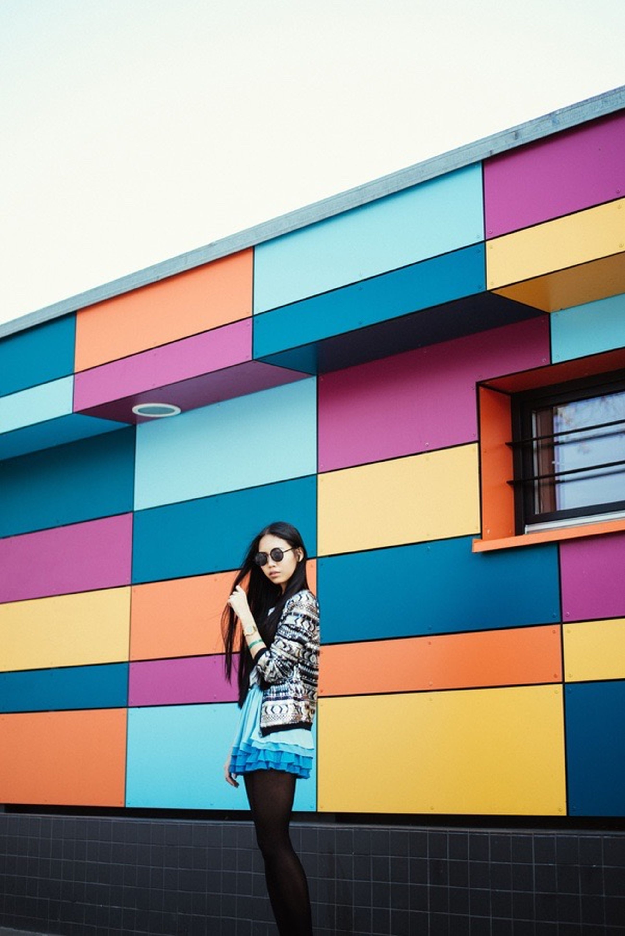 building exterior, architecture, built structure, lifestyles, casual clothing, standing, three quarter length, young adult, leisure activity, low angle view, person, front view, clear sky, building, multi colored, city, waist up, blue