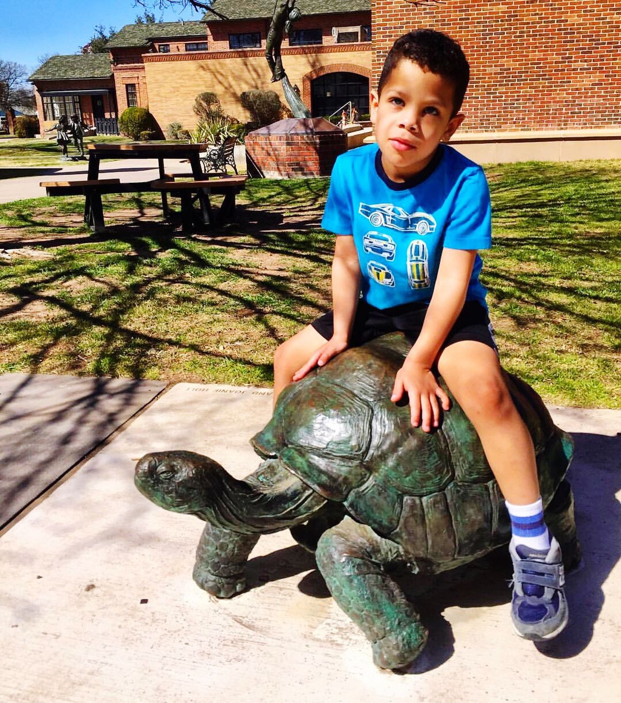 Boys One Person Childhood Portrait Children Only Child Outdoors Real People Sitting One Boy Only Full Length Happiness Smiling Playing People Day Tortoise Sculpture Museum Of The Southwest Midland, TX Childhood Memories
