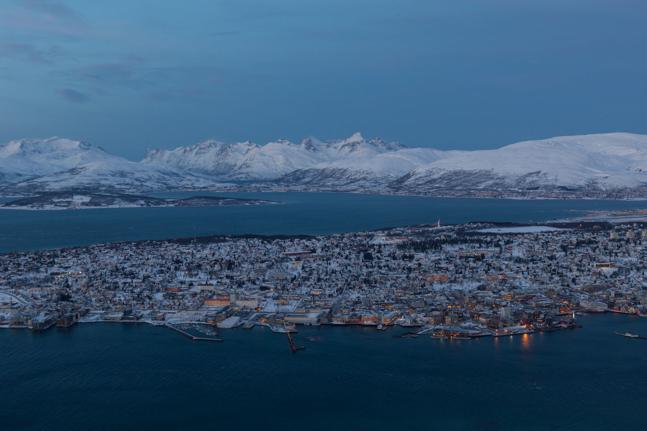 Town By Fjord With Snowcapped Mountains Against Sky