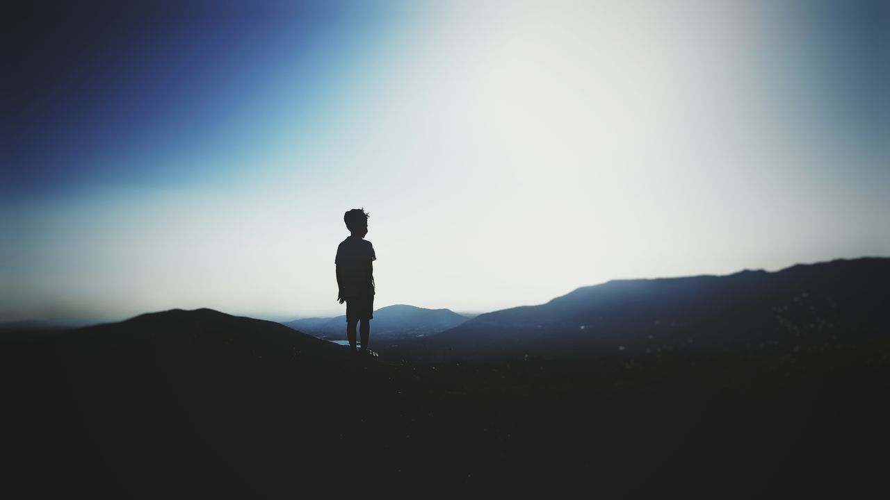 silhouette, standing, one person, clear sky, nature, landscape, real people, full length, sky, mountain, outdoors, scenics, sunset, beauty in nature, day, people