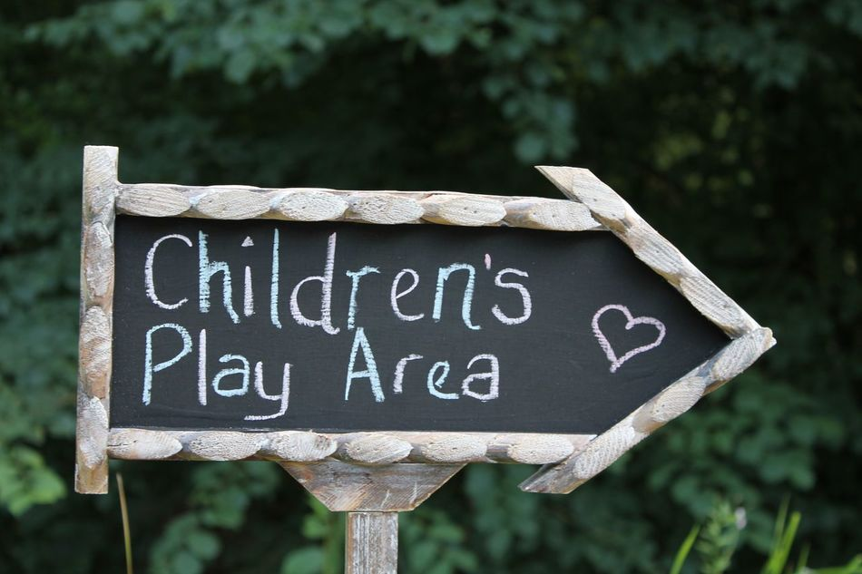 Children's play area sign Arrow Symbol Capital Letter Children Play Area Close-up Communication Guidance Information Information Sign Sign Text Western Script