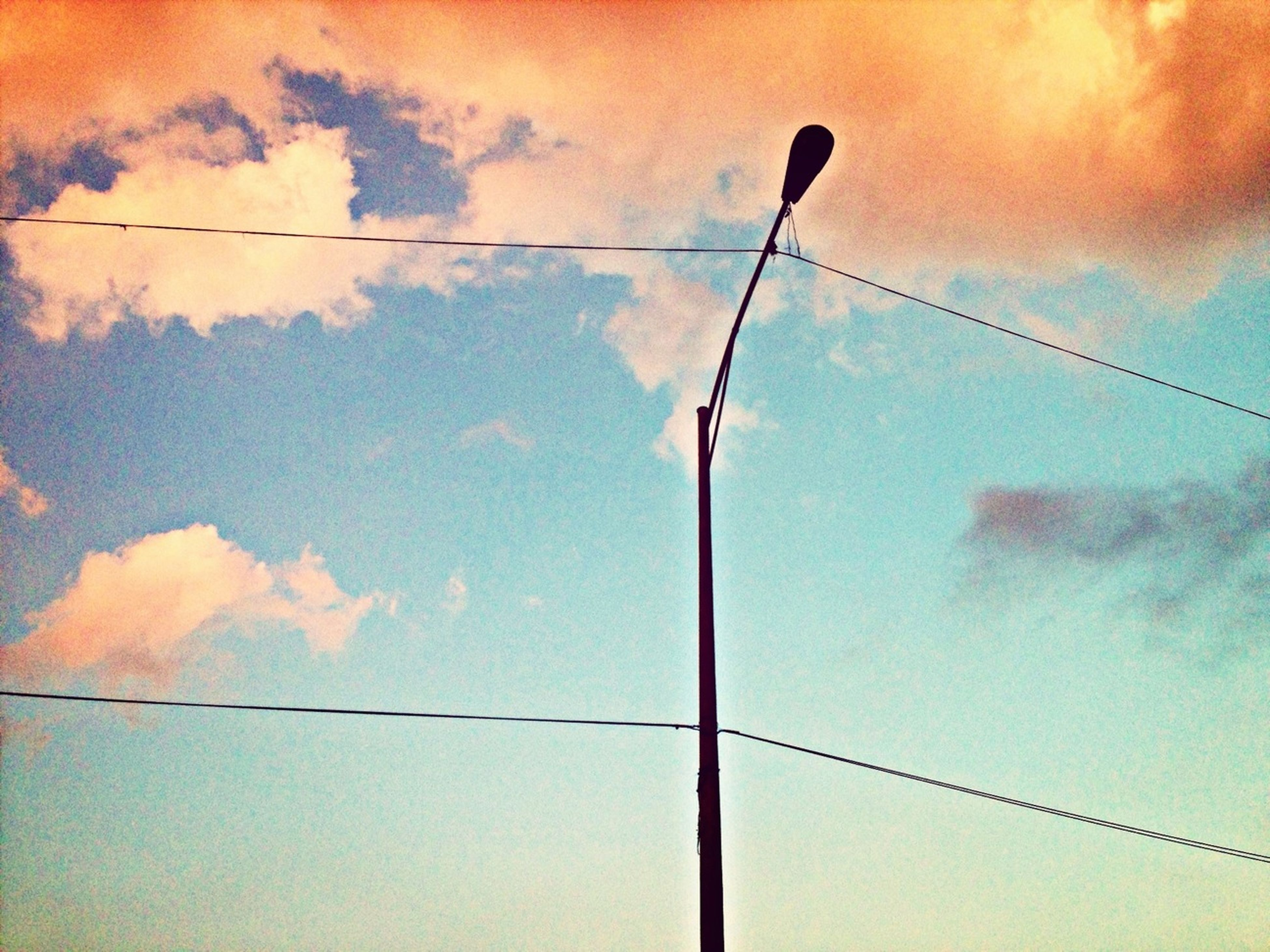 low angle view, power line, electricity, cable, power supply, sky, street light, lighting equipment, fuel and power generation, electricity pylon, technology, connection, pole, sunset, power cable, cloud - sky, silhouette, cloud, no people, outdoors