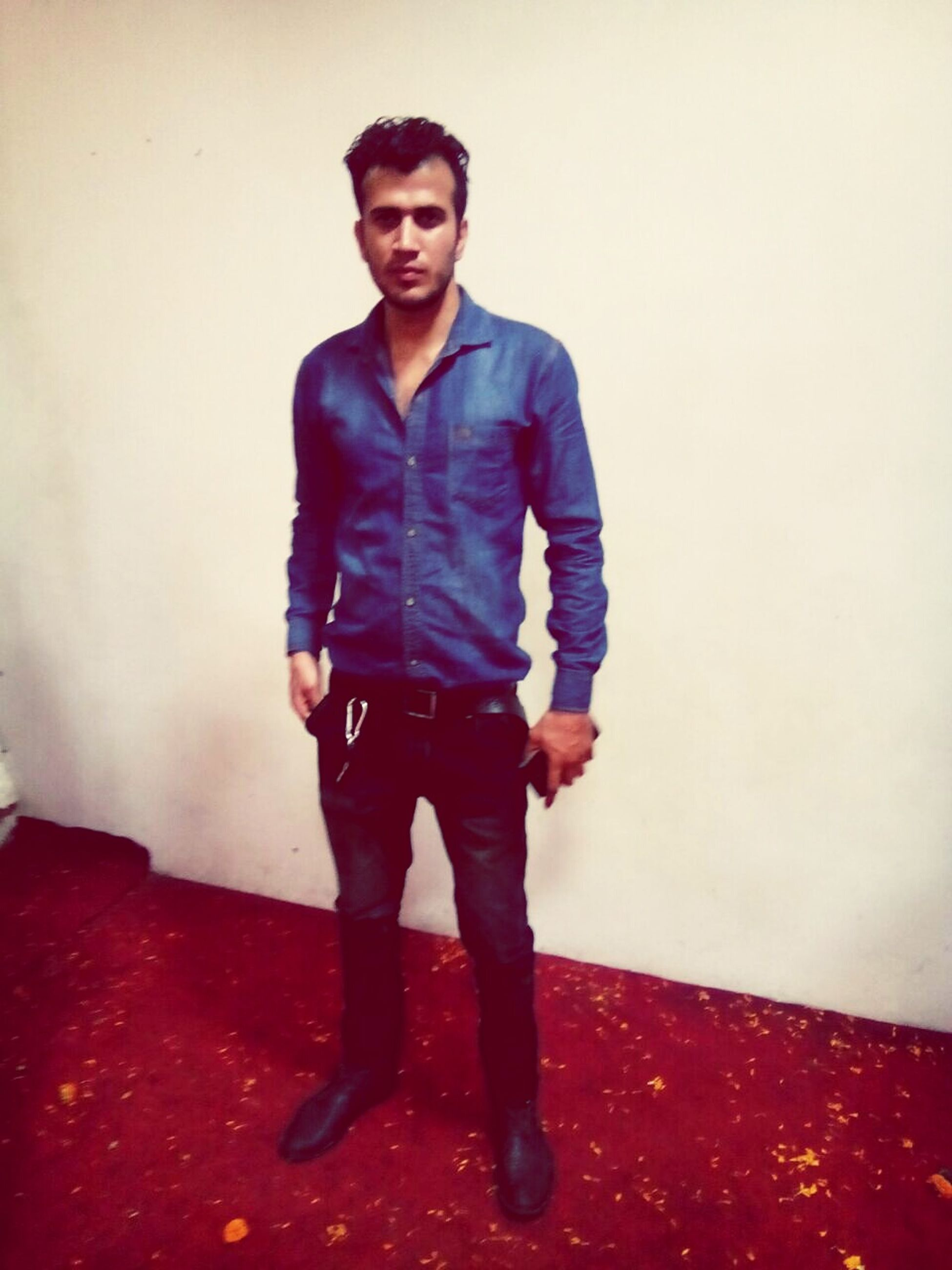 casual clothing, looking at camera, front view, portrait, standing, lifestyles, person, full length, young adult, wall - building feature, young men, leisure activity, three quarter length, copy space, smiling, indoors, happiness