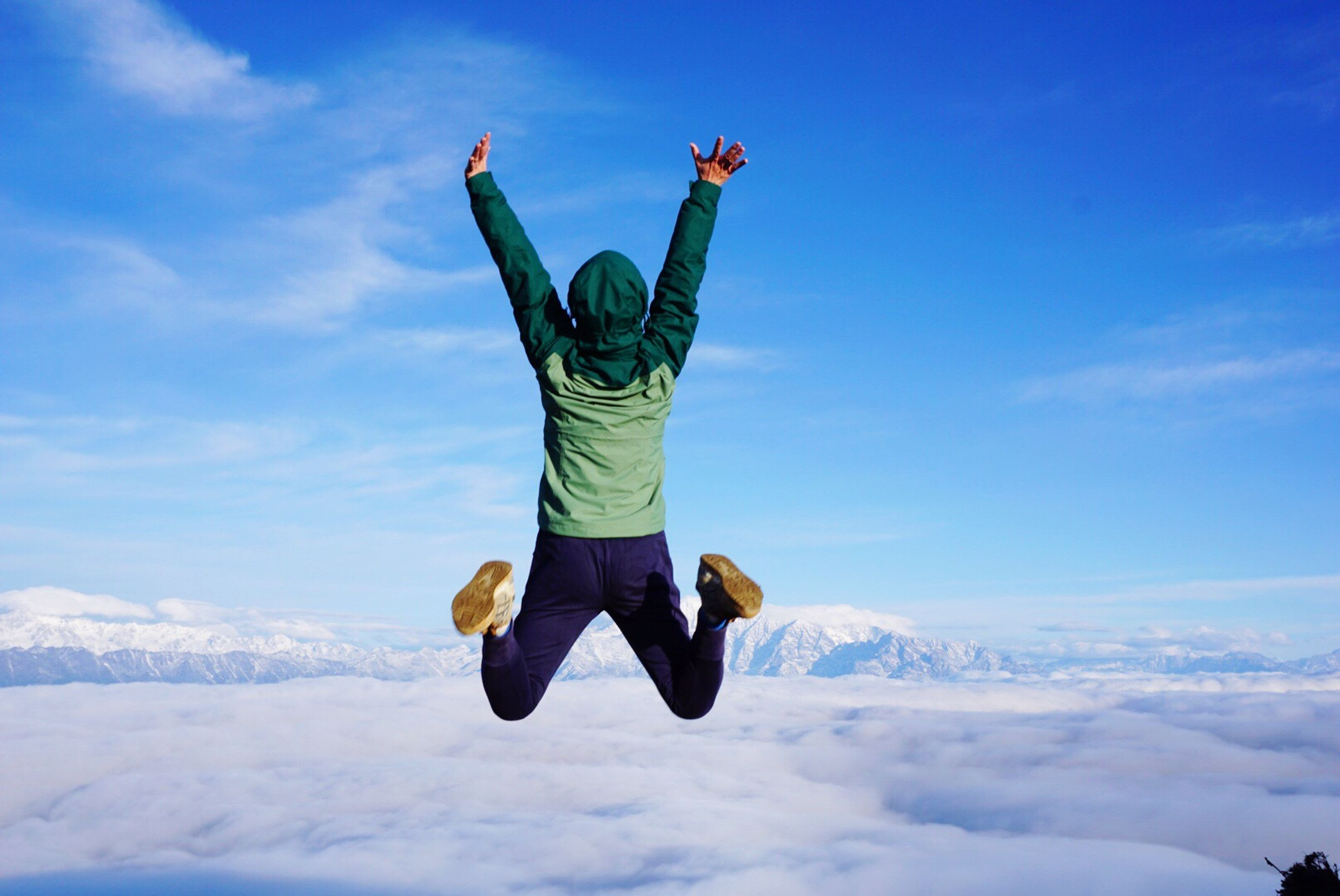 full length, lifestyles, leisure activity, mid-air, arms outstretched, freedom, sky, jumping, casual clothing, winter, blue, fun, snow, extreme sports, person, enjoyment, adventure, warm clothing