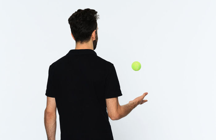 Adult Adults Only Ball Bouncing Day Holding Men Mid-air Motion One Man Only One Person Outdoors People Playing Real People Rear View Skill  Sport Studio Shot Tennis Tennis Ball Tennis Racket White Background Young Adult