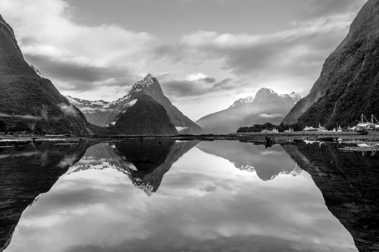 Misty mountain range and its reflection at Milford Sound, New Zealand in black and white Basin Beauty In Nature Cloud - Sky Day Fiordland Heritage Lake Landscape Mitre Monochrome Mountain Mountain Range National Park Nature No People Outdoors Piopiotahi Reflection Scenics Sky Tranquility Travel Destinations Vacations Water