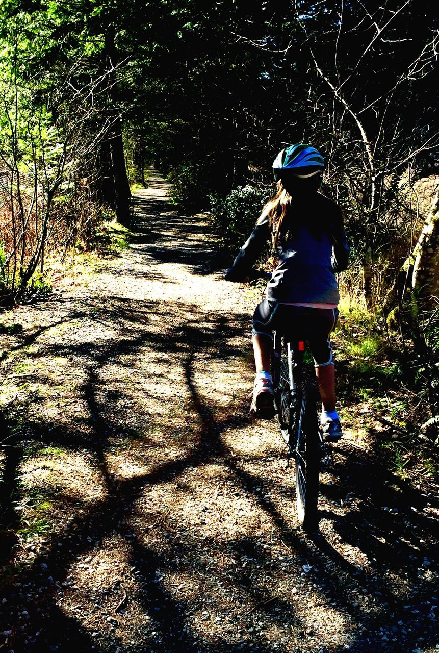 bicycle, shadow, cycling, sunlight, transportation, cycling helmet, riding, real people, tree, mountain bike, leisure activity, nature, rear view, full length, lifestyles, day, outdoors, headwear, land vehicle, healthy lifestyle, one person, beauty in nature, people