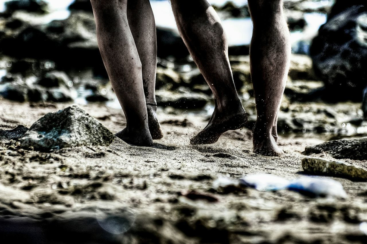 selective focus, low section, real people, human leg, day, sand, outdoors, rock - object, beach, standing, men, one person, close-up, nature, people
