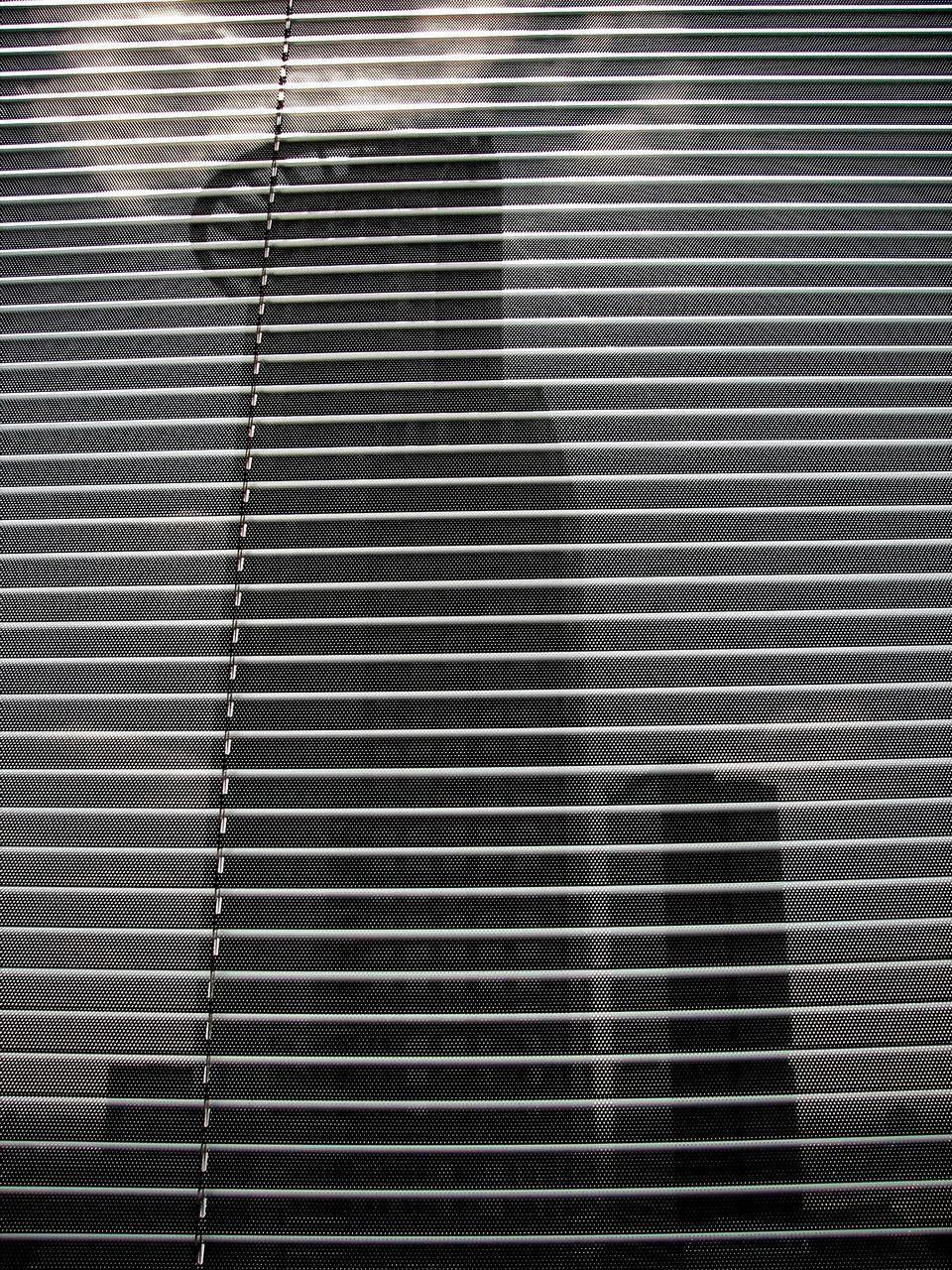 Tower Against Sky Seen Through Window Blinds