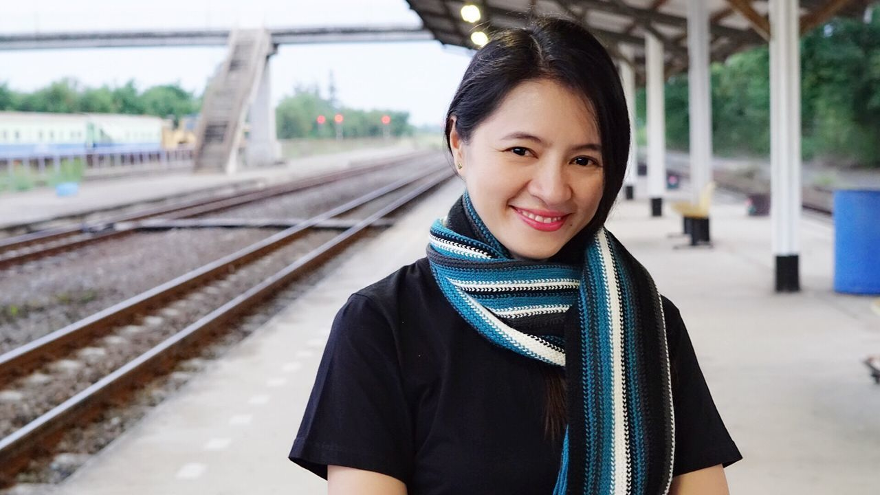 Travel Railroad Track Smiling Portrait Lifestyles Beauty Casual Clothing Waiting Railroad Station Passenger City Cultures Beautiful Woman Young Adult Adult Outdoors One Person Cheerful People