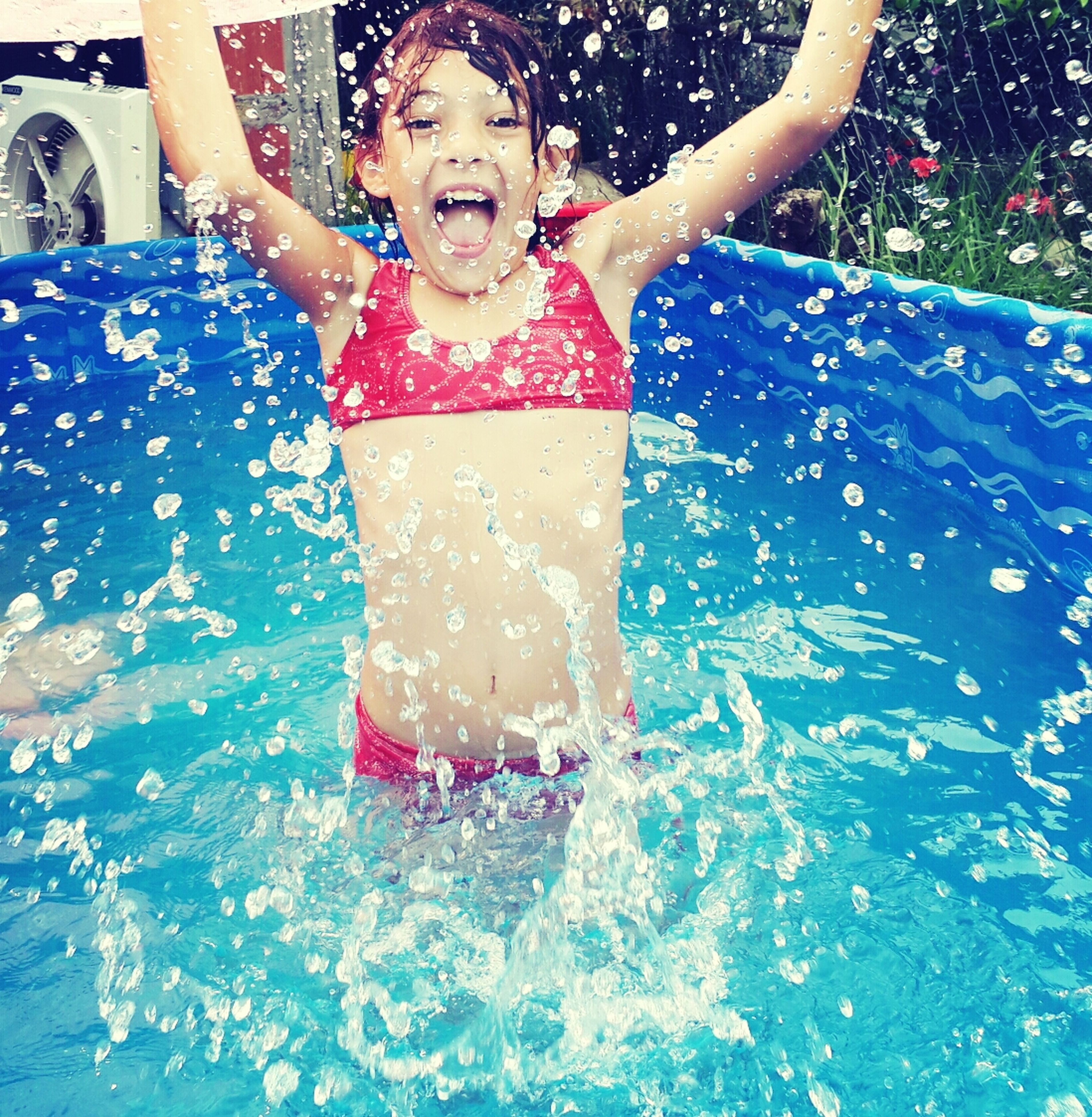 water, lifestyles, leisure activity, person, swimming pool, enjoyment, front view, fun, childhood, happiness, looking at camera, portrait, young adult, smiling, elementary age, vacations, girls, full length
