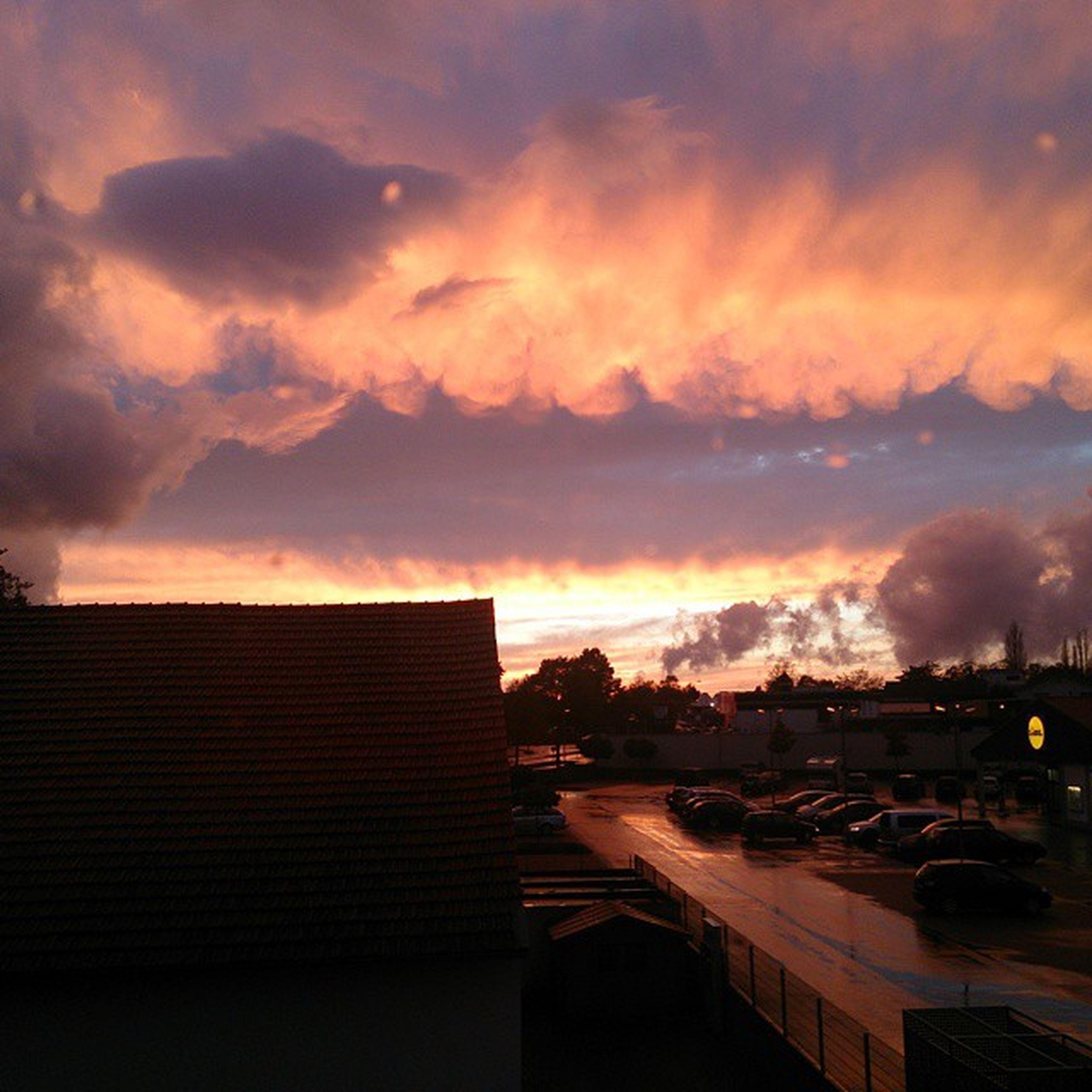 sunset, sky, architecture, building exterior, cloud - sky, built structure, orange color, city, cloudy, transportation, dramatic sky, cloud, dusk, weather, road, silhouette, overcast, car, illuminated, outdoors