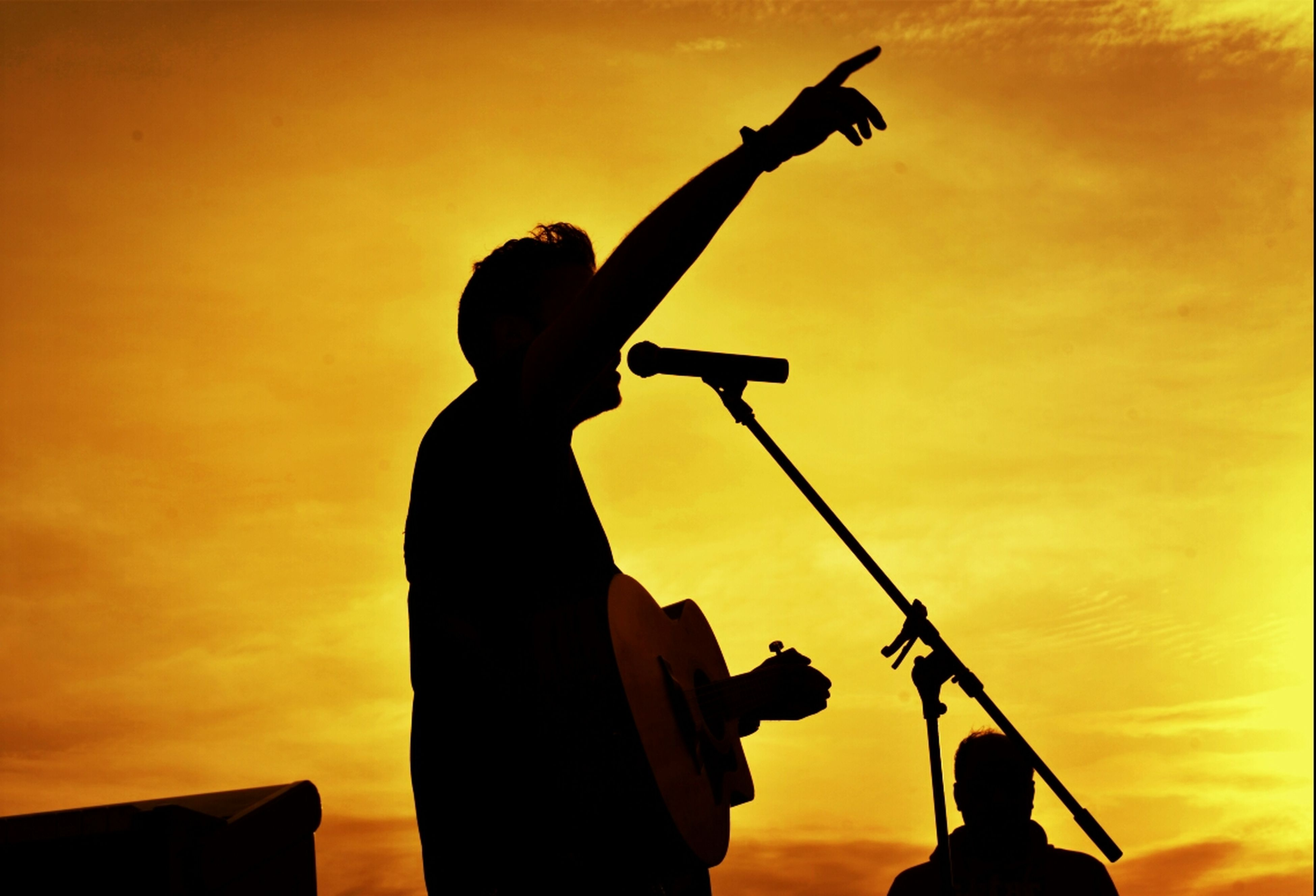 silhouette, sunset, men, lifestyles, leisure activity, low angle view, technology, holding, photography themes, orange color, sky, musical instrument, standing, photographing, music, arts culture and entertainment, camera - photographic equipment, performance