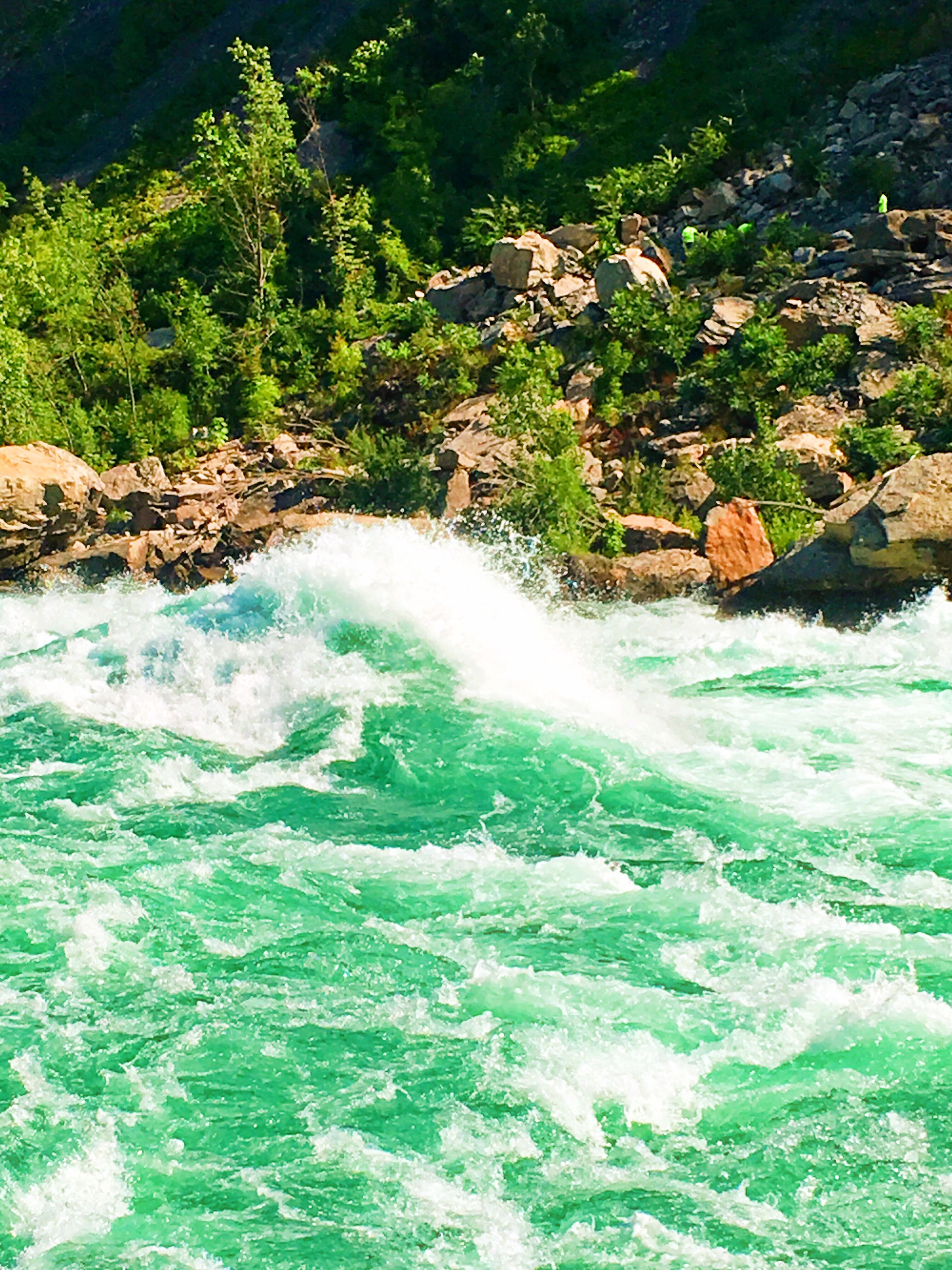 water, waterfront, motion, river, flowing water, rock - object, beauty in nature, flowing, nature, scenics, surf, environment, wave, stream, green color, day, non-urban scene, sea, outdoors, rock formation, tranquil scene, remote, natural landmark, power in nature, physical geography, lush foliage, no people