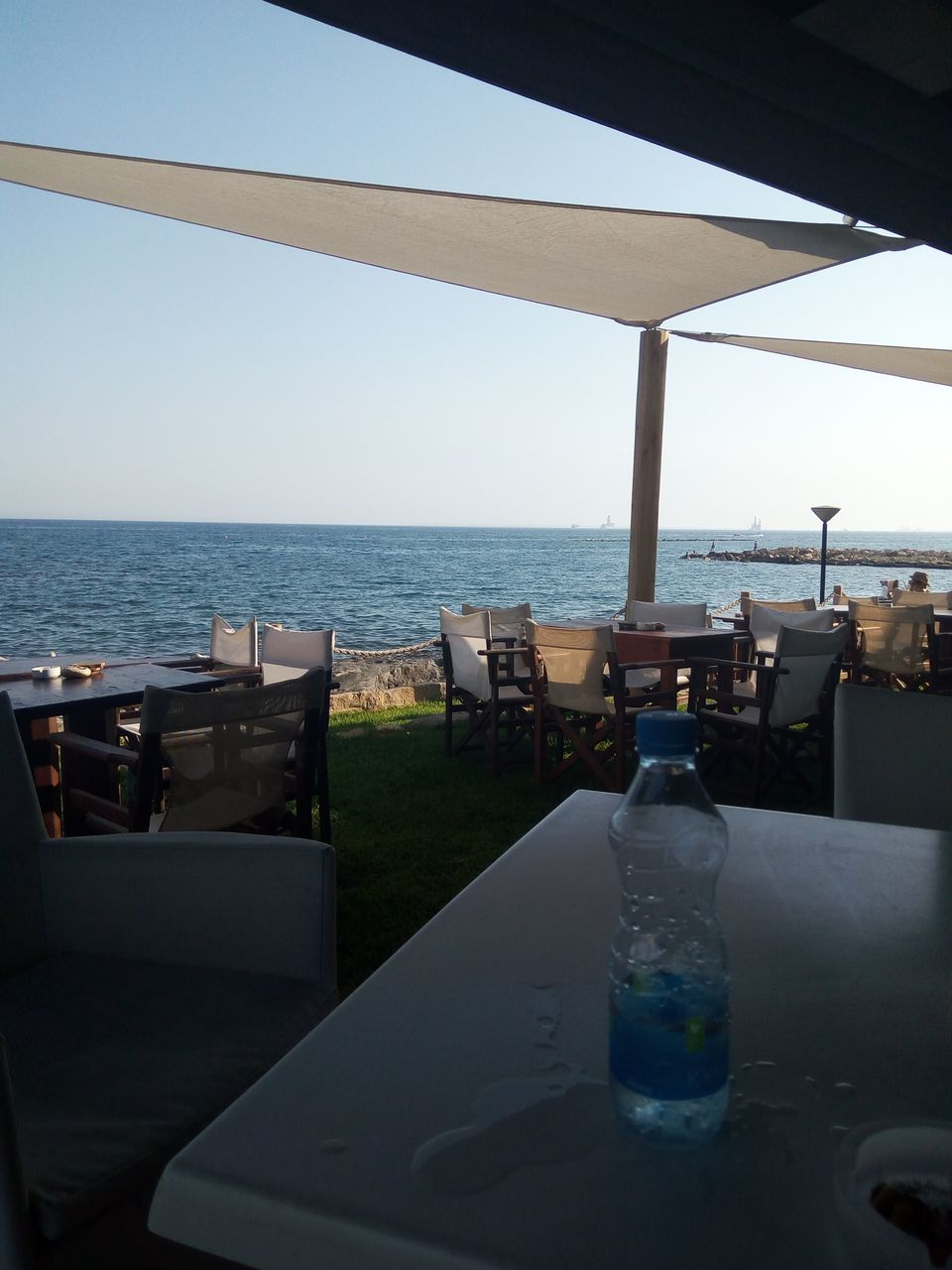 sea, water, chair, table, bottle, horizon over water, drink, no people, nature, clear sky, day, sky, outdoors, beauty in nature, close-up