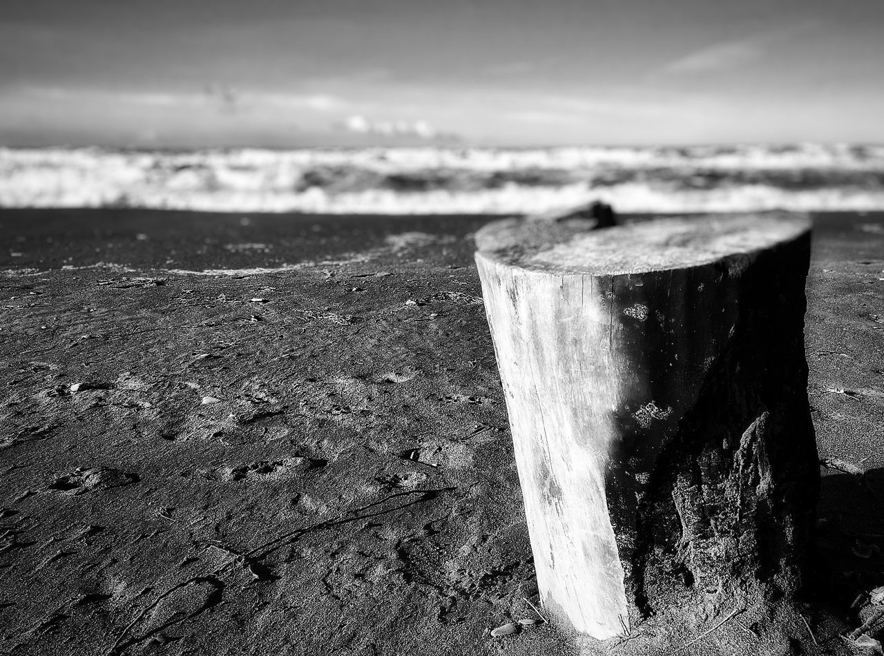 water, sea, beach, close-up, horizon over water, focus on foreground, sky, shore, wet, selective focus, sunlight, sand, day, outdoors, nature, no people, part of, metal, shadow, tranquility