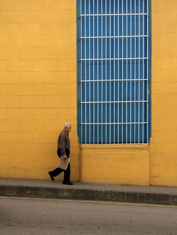 Señor mayor caminando frente a una pared amarilla Architecture Blue Building Exterior Built Structure Day Old Person Outdoors People Street Streetphotography Window Yellow