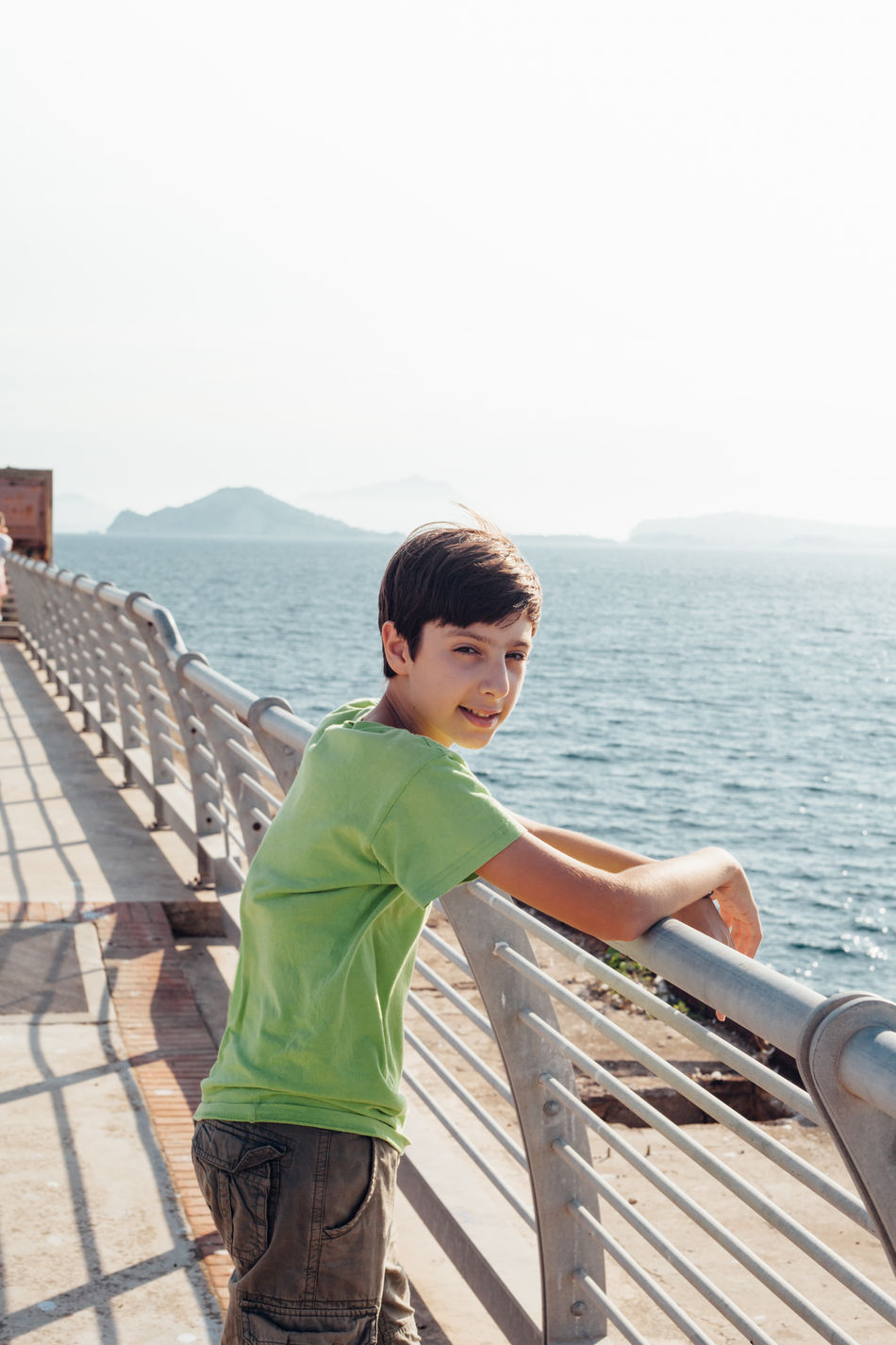 Happy boy on a sea promenade, bay of Naples, Italy Bay Of Naples Beauty In Nature Casual Clothing Clear Sky Day Leisure Activity Lifestyles Mountain Naples, Italy Napoli Nature One Person Outdoors People Railing Real People Scenics Sea Sky Water Wood - Material Wood Paneling Young Adult