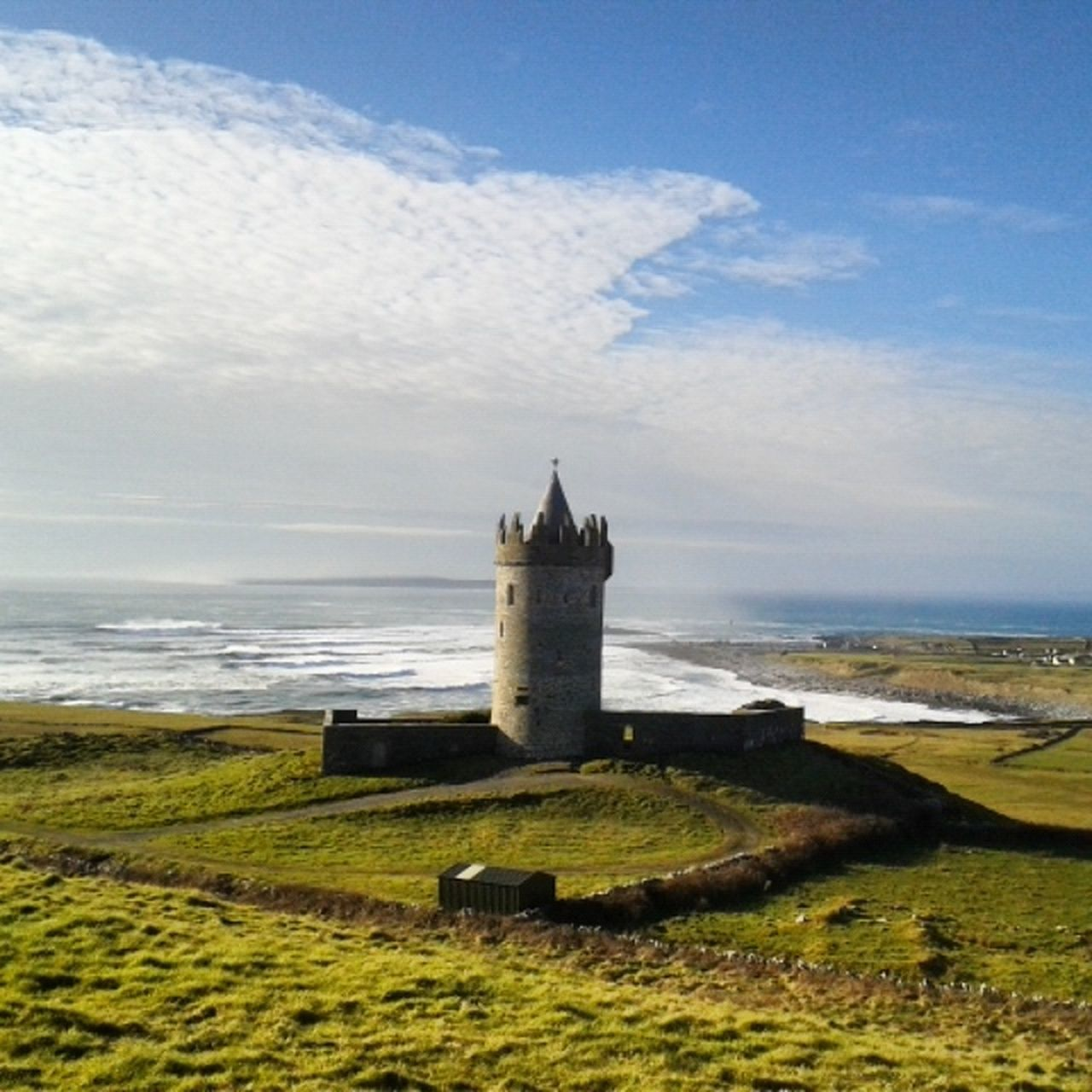 sea, history, sky, water, horizon over water, architecture, day, tower, built structure, cloud - sky, beach, no people, nature, outdoors, tranquility, castle, scenics, building exterior, lighthouse, beauty in nature, grass