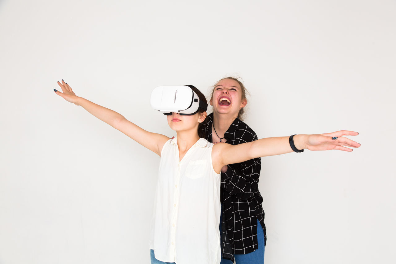 Laughing enjoying virtual reality experience with open arms 3D Augmented Reality Enjoyment Entertainment Friendship Full Frame Fun Futuristic Game Happiness Head Mounted Display Hm HMD Leisure Activity Recreational Pursuit Smiling Studio Shot Three Dimensional Two People Virtual Reality Headset Virtual Reality Simulator Vr White Background Young Adult Young Women The Portraitist - 2017 EyeEm Awards