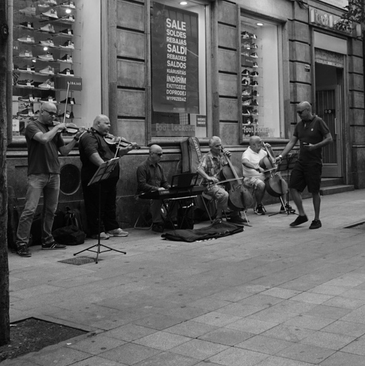 real people, men, street, music, building exterior, full length, built structure, large group of people, musical instrument, musician, architecture, casual clothing, lifestyles, women, outdoors, standing, city, day, guitar, adult, people, adults only