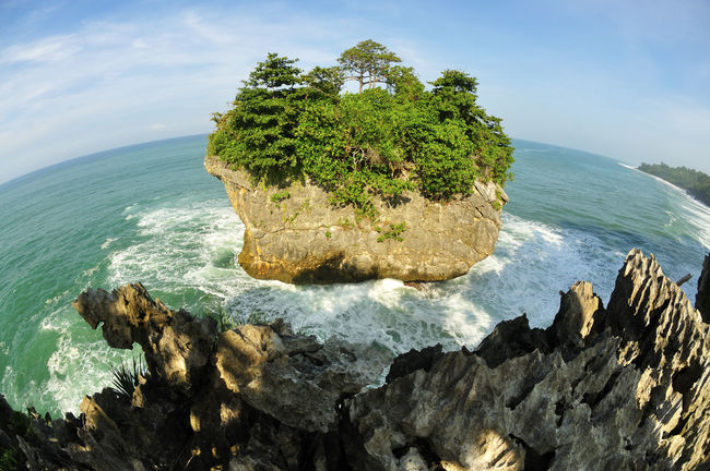 """Beautiful fisheye view of """"Karang Bokor"""" at Sawarna beach in Indonesia Beauty In Nature Blue Cliff Cloud Cloud - Sky Coastline Day Growth Horizon Over Water Idyllic Nature No People Non Urban Scene Non-urban Scene Outdoors Remote Rock Rock - Object Rock Formation Scenics Sea Sky Tranquil Scene Tranquility Water"""