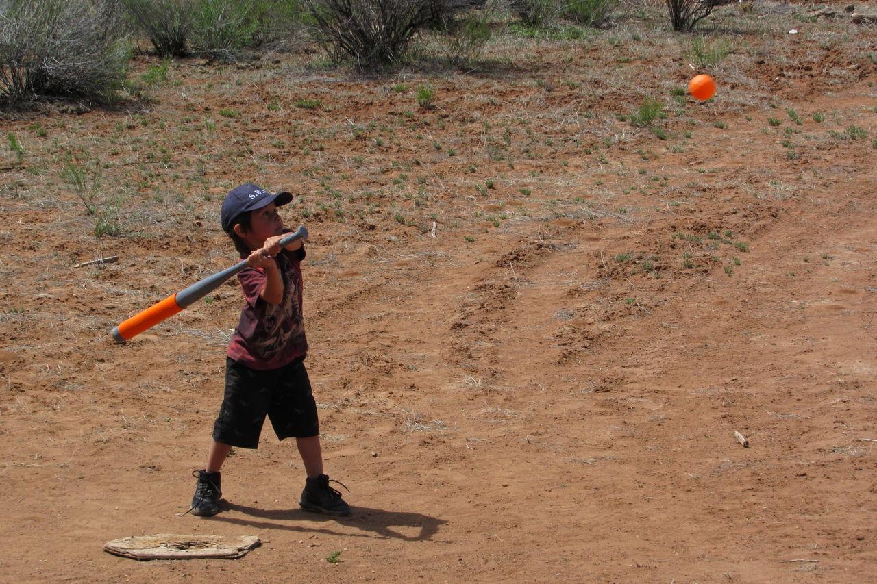 Full Length Of Boy Playing Baseball On Field