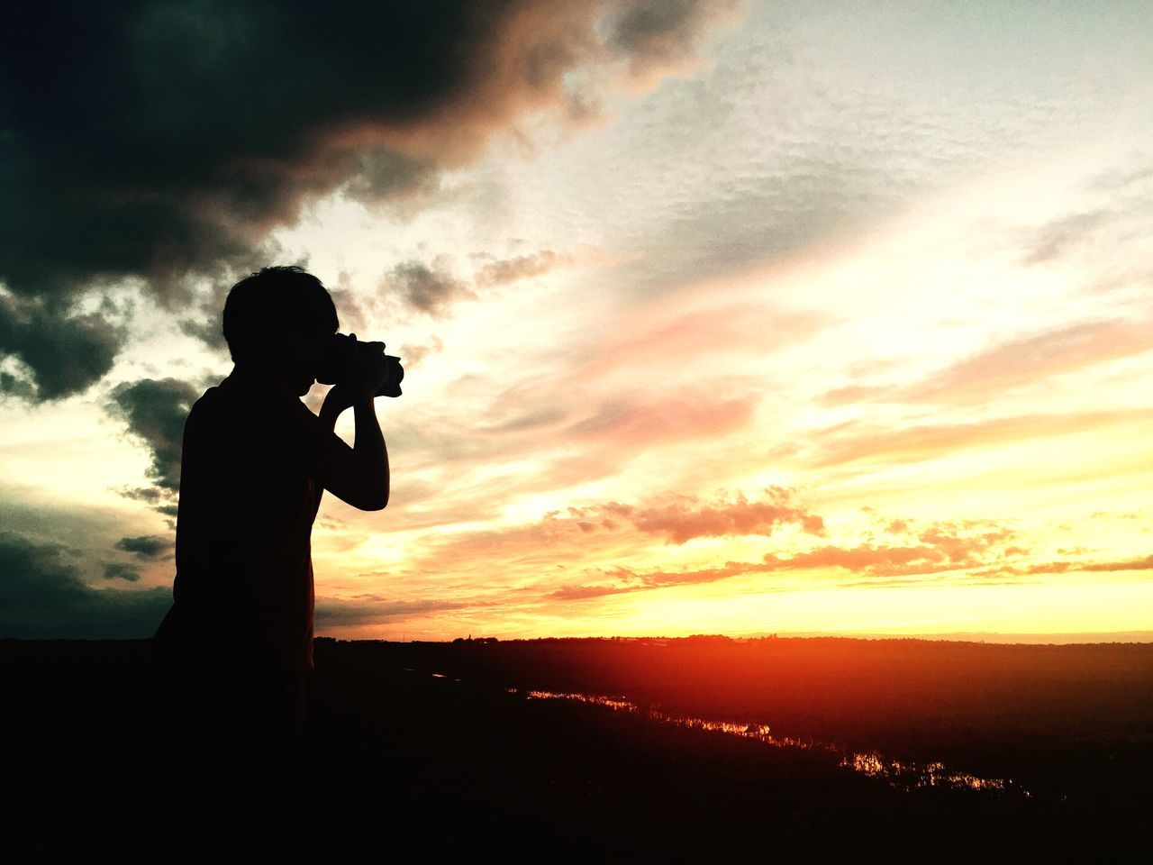 Sunset Cloud - Sky Silhouette Photographing Photography Themes Sky Camera - Photographic Equipment One Person Real People Photographer Nature Standing Beauty In Nature Leisure Activity Lifestyles Technology Digital Camera Outdoors Holding Scenics