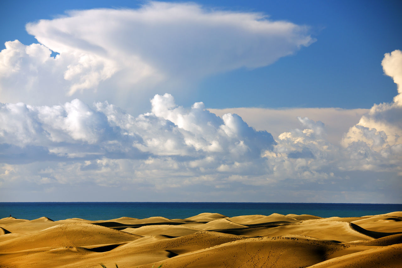 Scenic View Of Desert And Sea Against Cloudy Sky