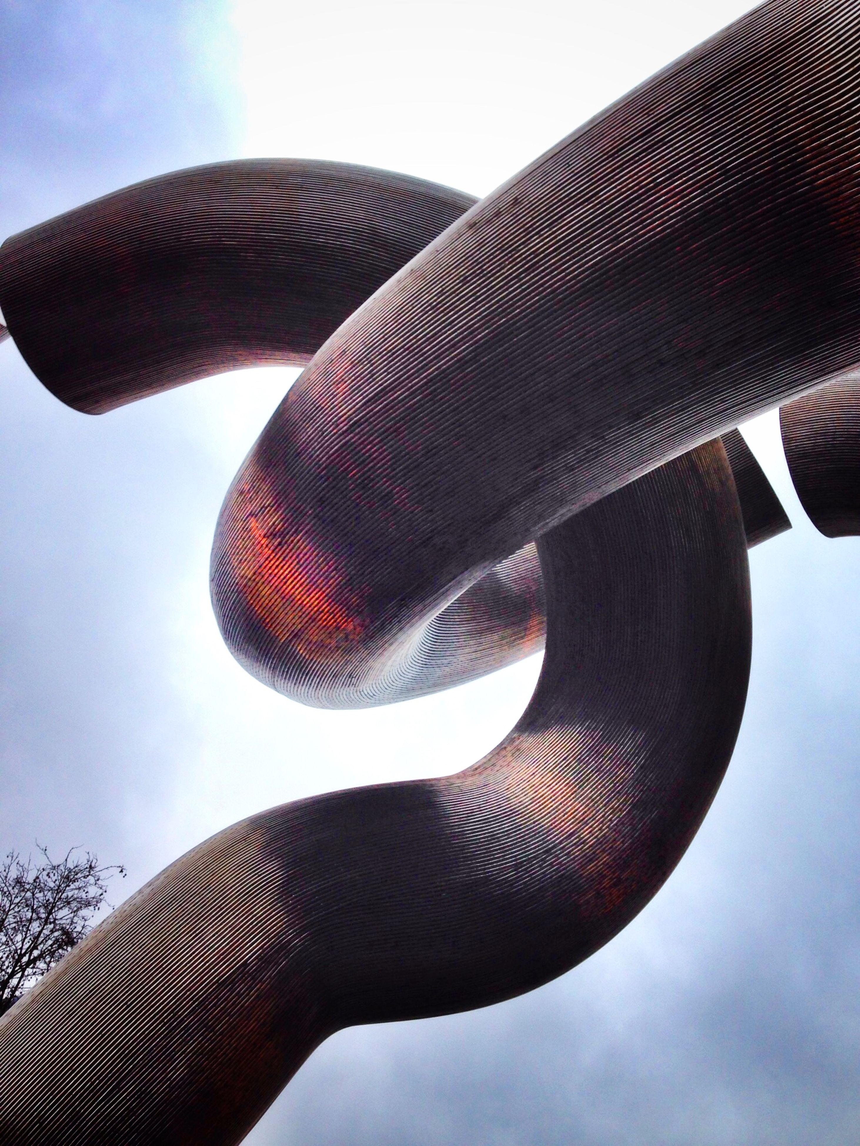 low angle view, sky, blue, sunlight, no people, outdoors, close-up, part of, day, pattern, spiral, nature, clear sky, one animal, animal themes, cloud - sky, sculpture, animals in the wild, metal, cloud