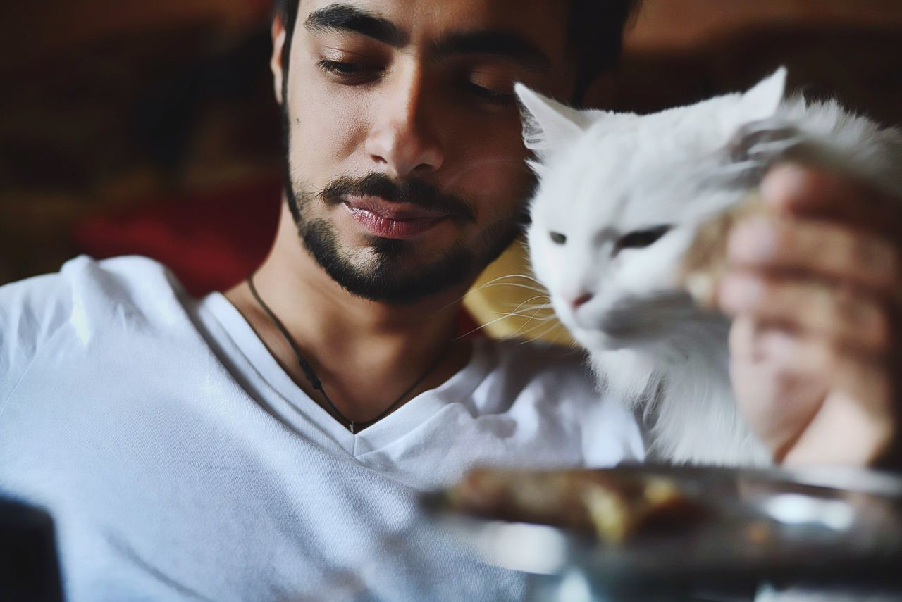 Close-Up Of Young Man With Cat Sitting At Home