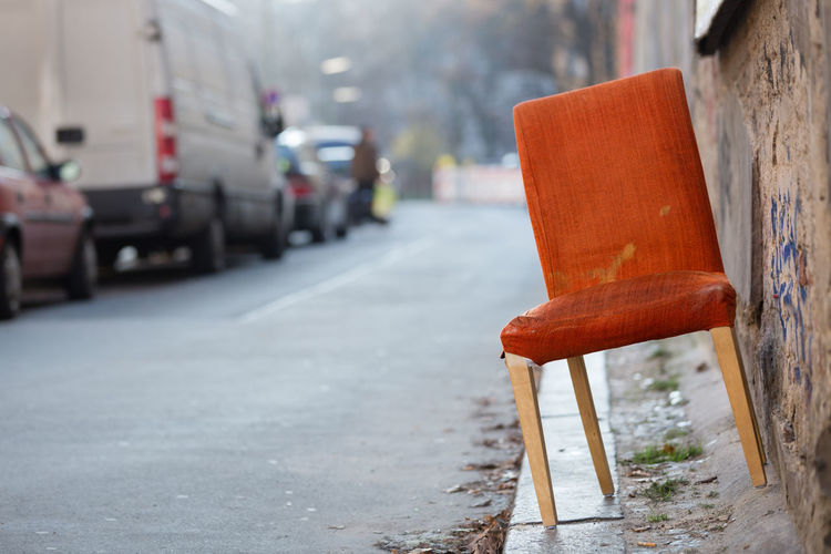 Berlin's abandoned chairs. Last step before disposal of old, orange colored chair on curb. Abandoned Aging Process Architecture Bad Condition Chair City Cityscape Curb Damaged Day Deterioration Empty No People Obsolete Old Orange Color Outdoors Red Retirement Seat Selective Focus Single Object Transportation Wall - Building Feature Weathered