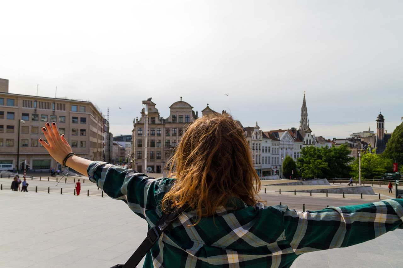 Happy young girl open her arms to the sky Architecture Arms Arms Raised Building Exterior Built Structure City City Life Cityscape Czech Republic Day Focus On Foreground Girl Green Hair Long Hair Outdoors Peace Peace And Quiet Person Prague Residential District Shirt Sky Tourism Vacations