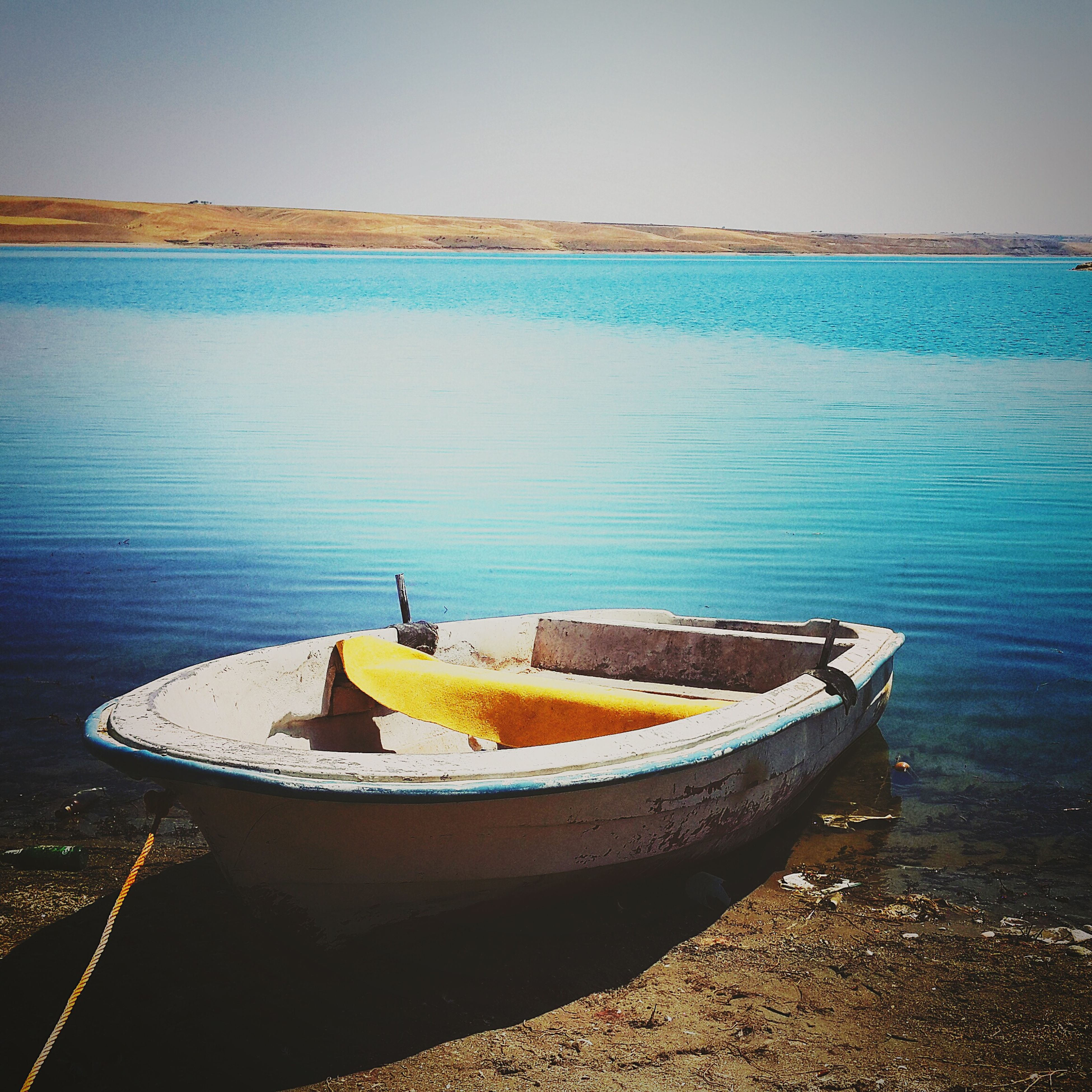 water, sea, nautical vessel, boat, moored, beach, blue, tranquility, shore, tranquil scene, sky, transportation, nature, scenics, horizon over water, beauty in nature, outdoors, mode of transport, day, no people