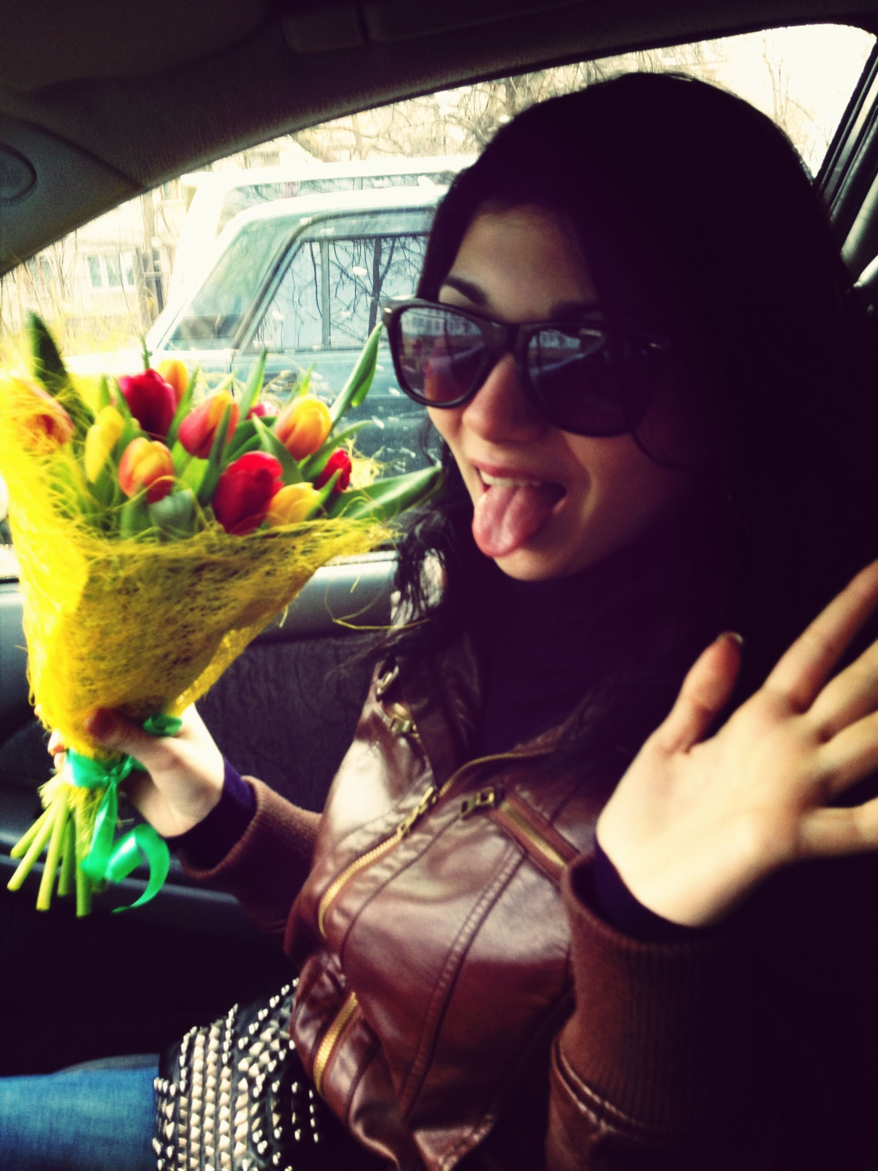 lifestyles, holding, person, leisure activity, young adult, young women, casual clothing, front view, looking at camera, portrait, indoors, sunglasses, sitting, smiling, flower, car, headshot, freshness