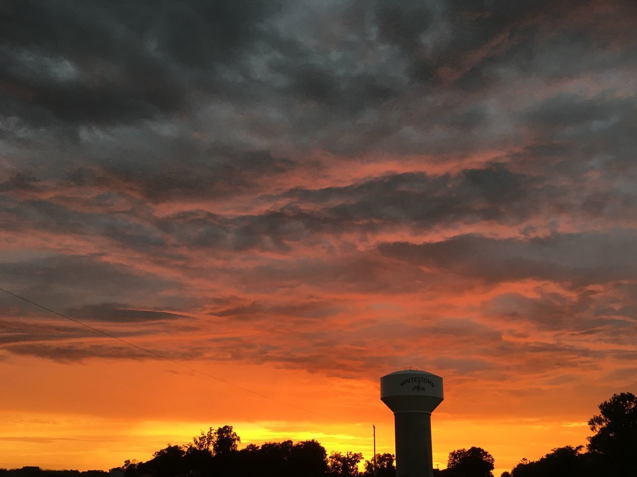 Water Tower Amidst Trees Against Cloudy Sky During Sunset