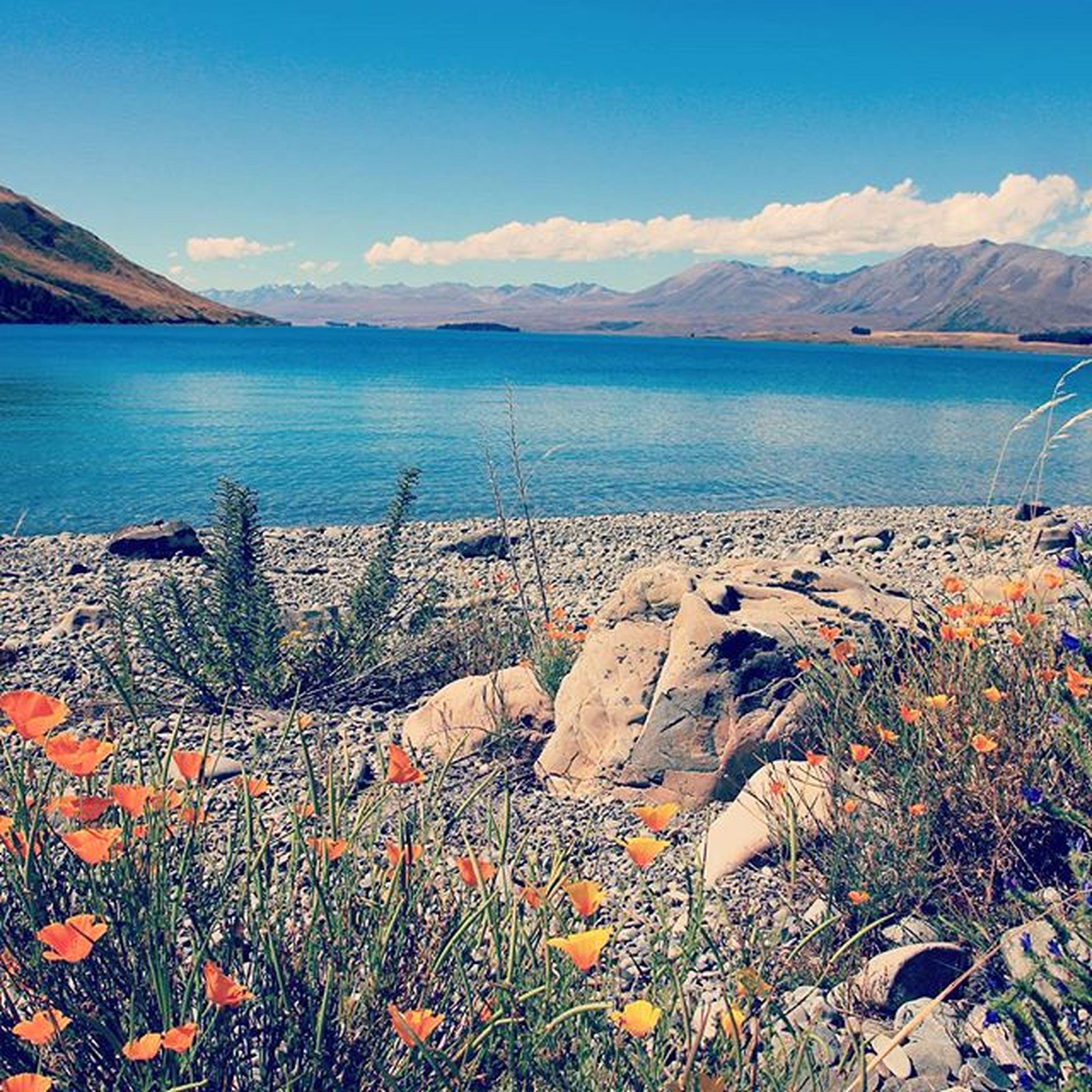 water, tranquil scene, mountain, tranquility, scenics, beauty in nature, sky, sea, nature, mountain range, blue, lake, idyllic, landscape, non-urban scene, beach, remote, calm, coastline, shore
