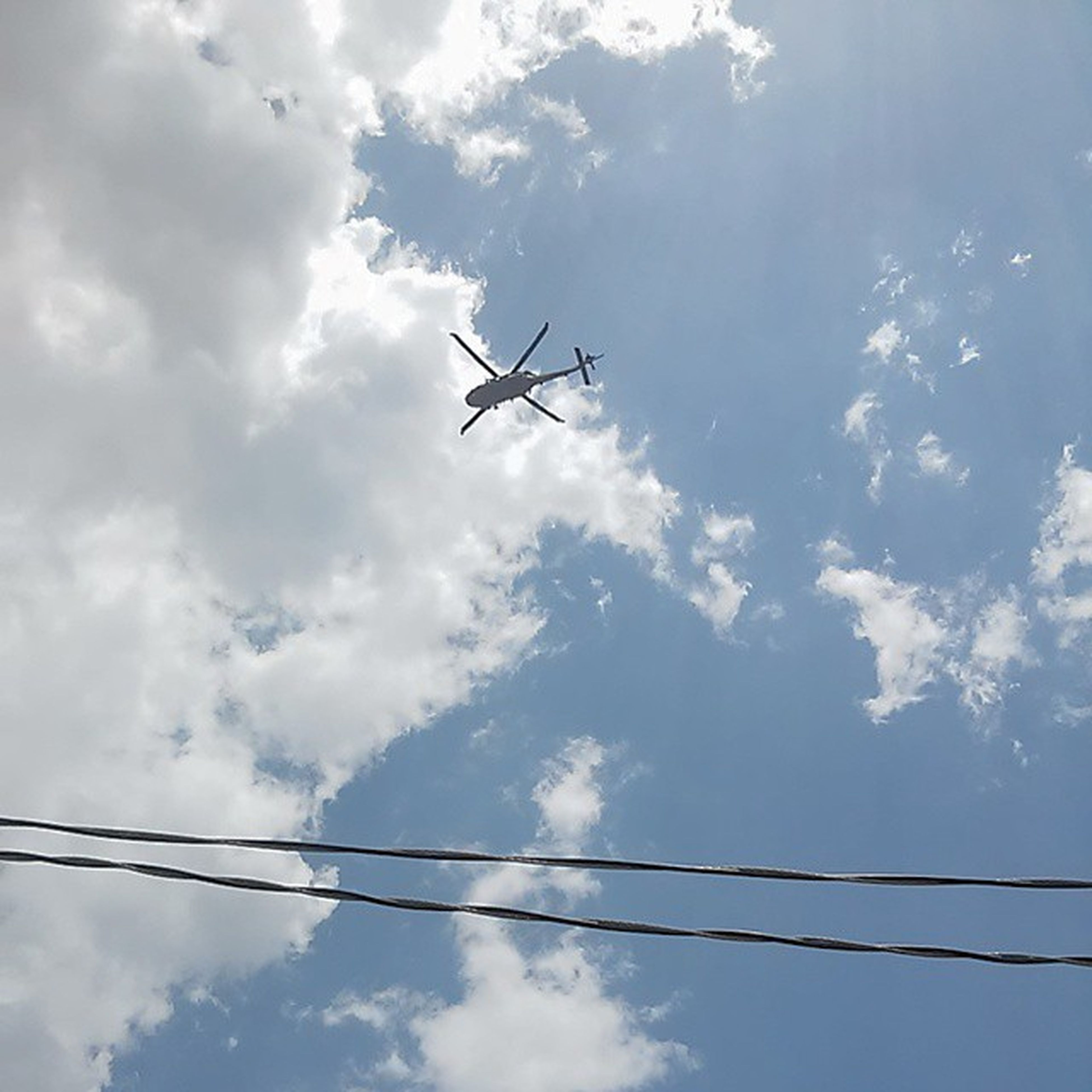 low angle view, sky, airplane, flying, transportation, air vehicle, cloud - sky, mode of transport, cloudy, cloud, blue, journey, day, mid-air, outdoors, nature, technology, power line, no people, electricity