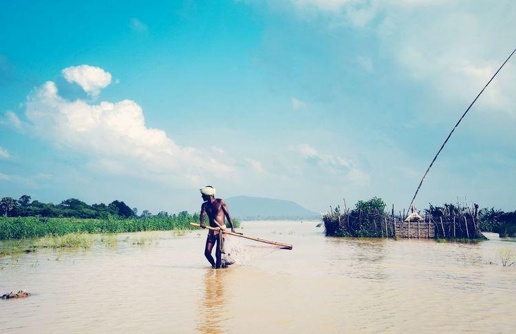 Subsistence fisherman trawling for fish. Fisherman Livelihood Lifestyle People People Watching People At Work Men At Work  Monsoon High Tide River In Spate