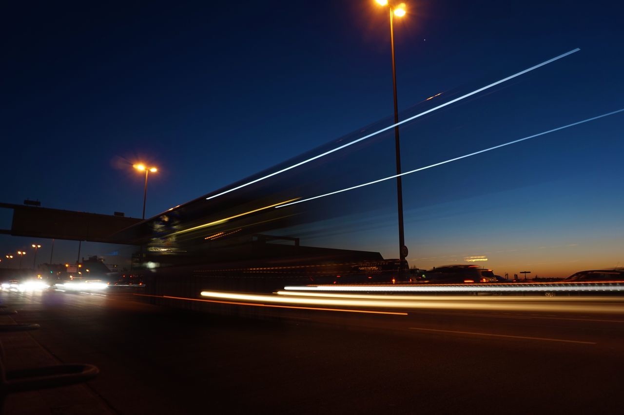 illuminated, night, light trail, transportation, speed, long exposure, street light, blurred motion, motion, road, moon, no people, high street, outdoors, land vehicle, sky, architecture, city