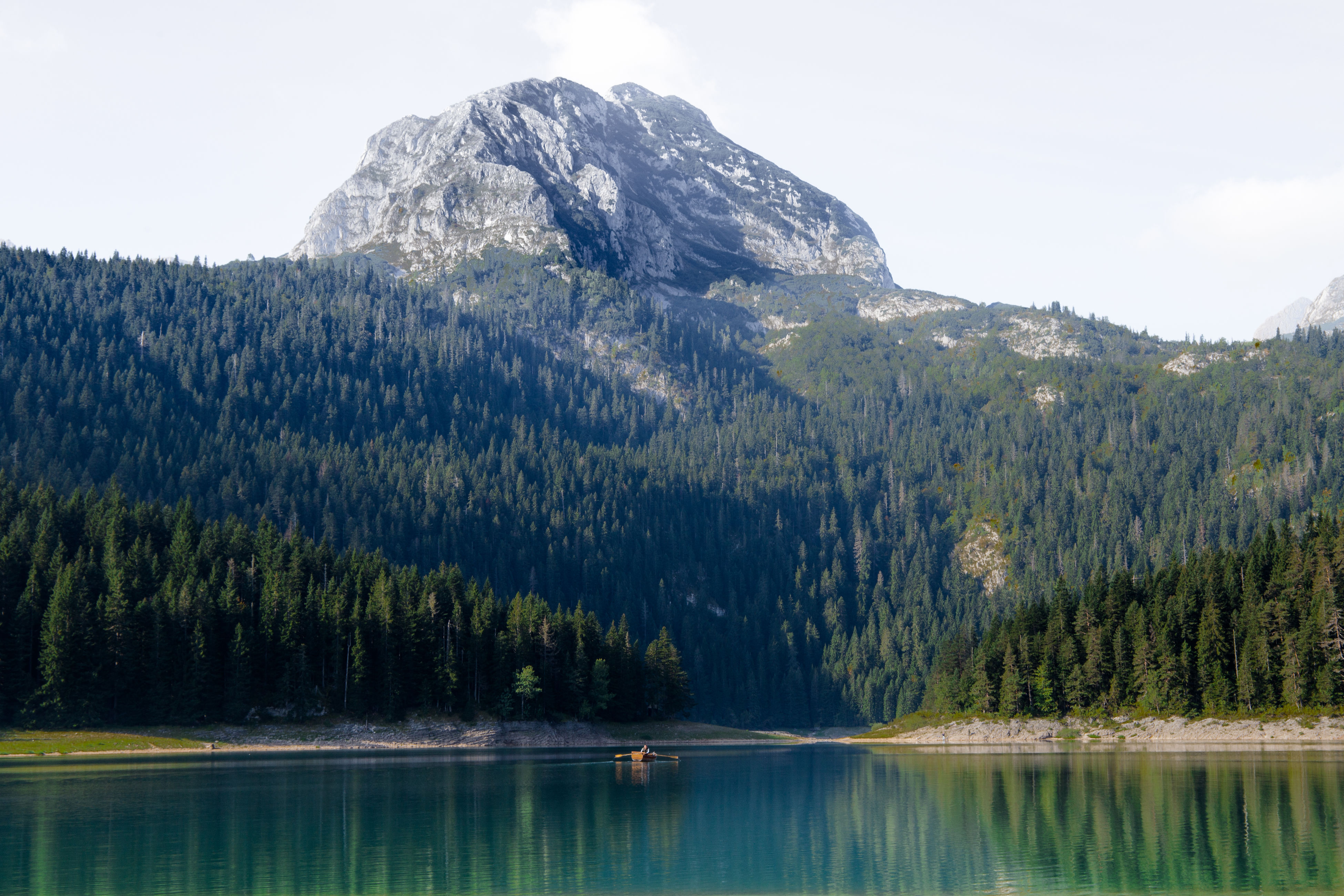 Distant Boat On Black Lake In Durmitor National Park