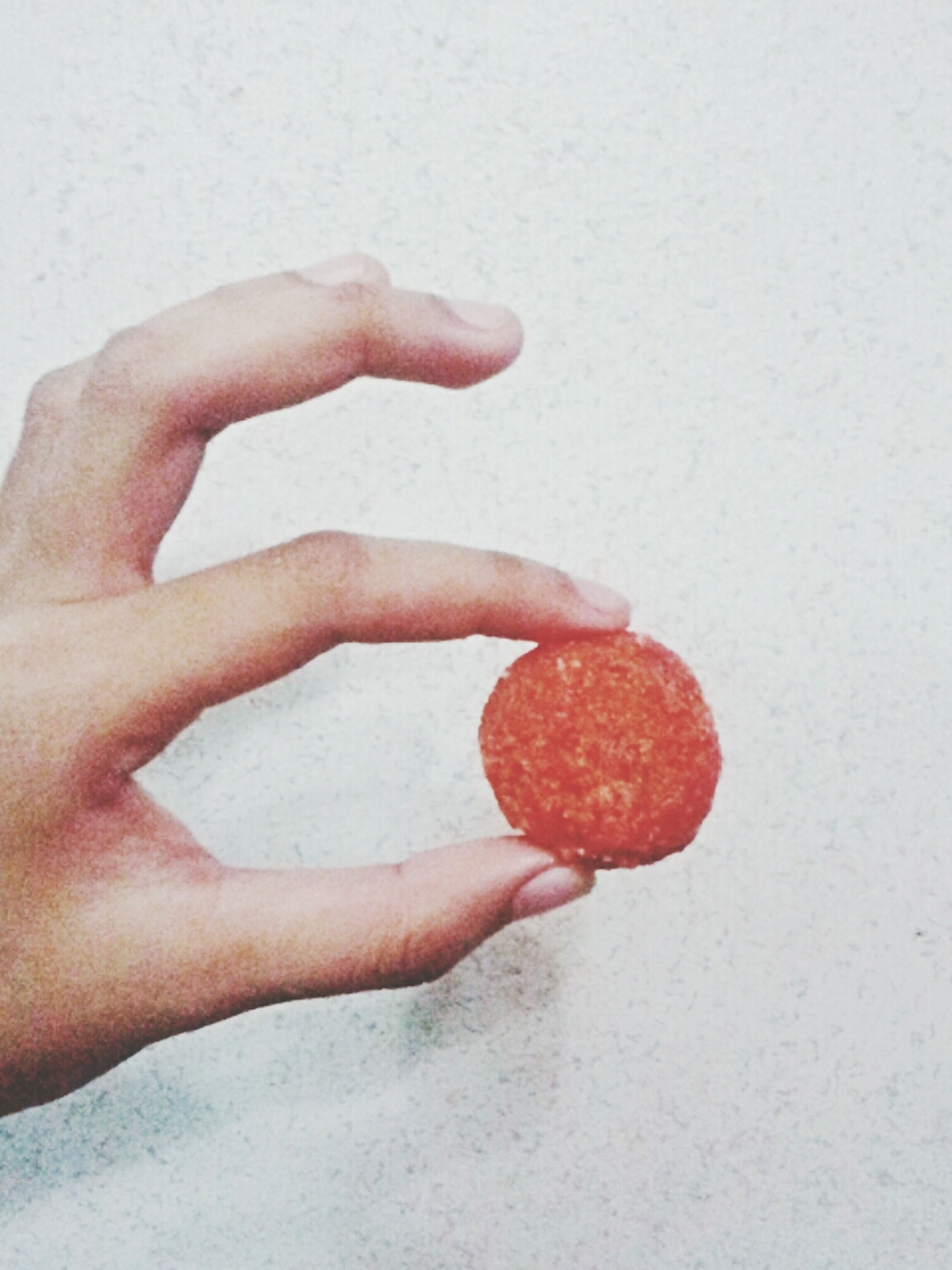 person, food and drink, holding, food, part of, fruit, cropped, red, healthy eating, indoors, freshness, close-up, human finger, unrecognizable person, wall - building feature, personal perspective, studio shot