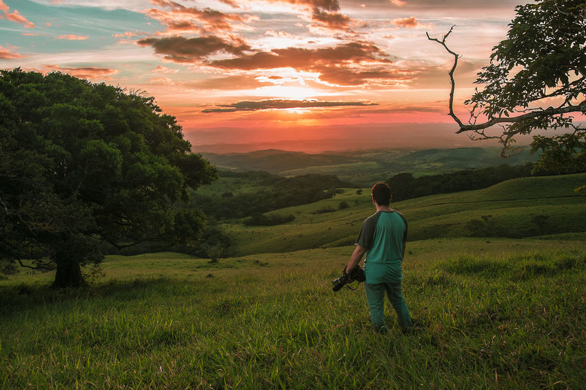 Captando atardeceres en la provincia de Guanacaste Beauty In Nature Day Full Length Grass Landscape Lifestyles Nature One Person Outdoors Real People Sky Sunset Tranquil Scene Tree Walking